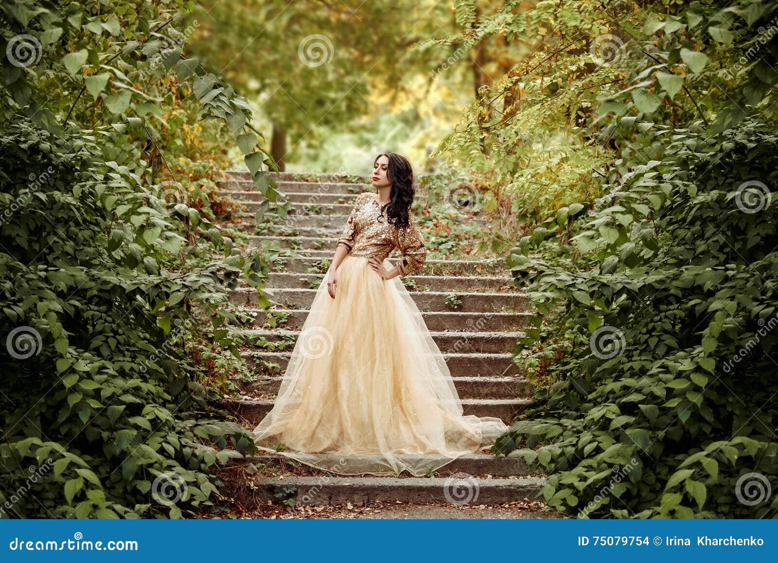 Härlig flicka i en guld, lyxig klänning