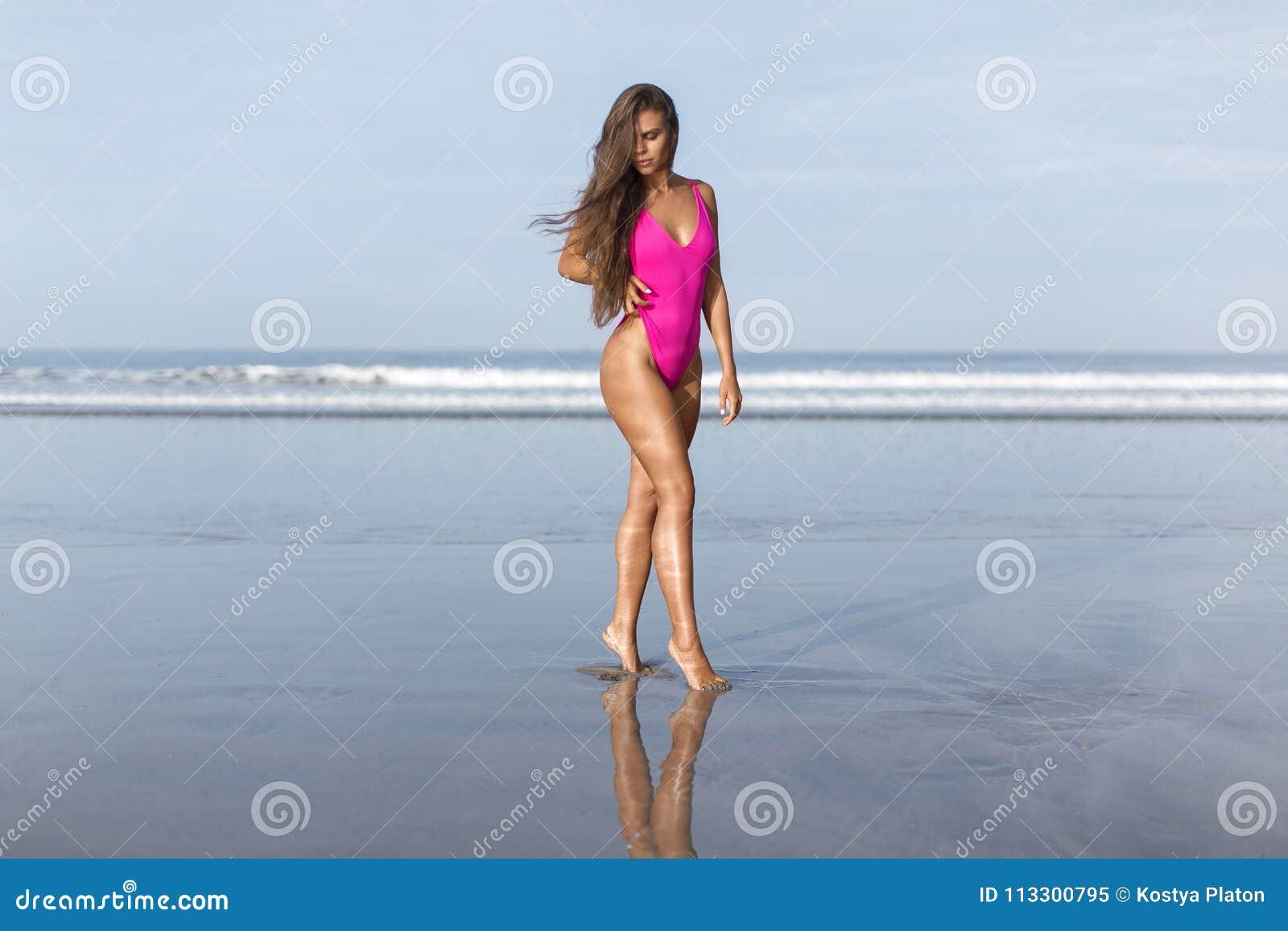 Härlig flicka i en rosa baddräkt på det blåa havet på gryning