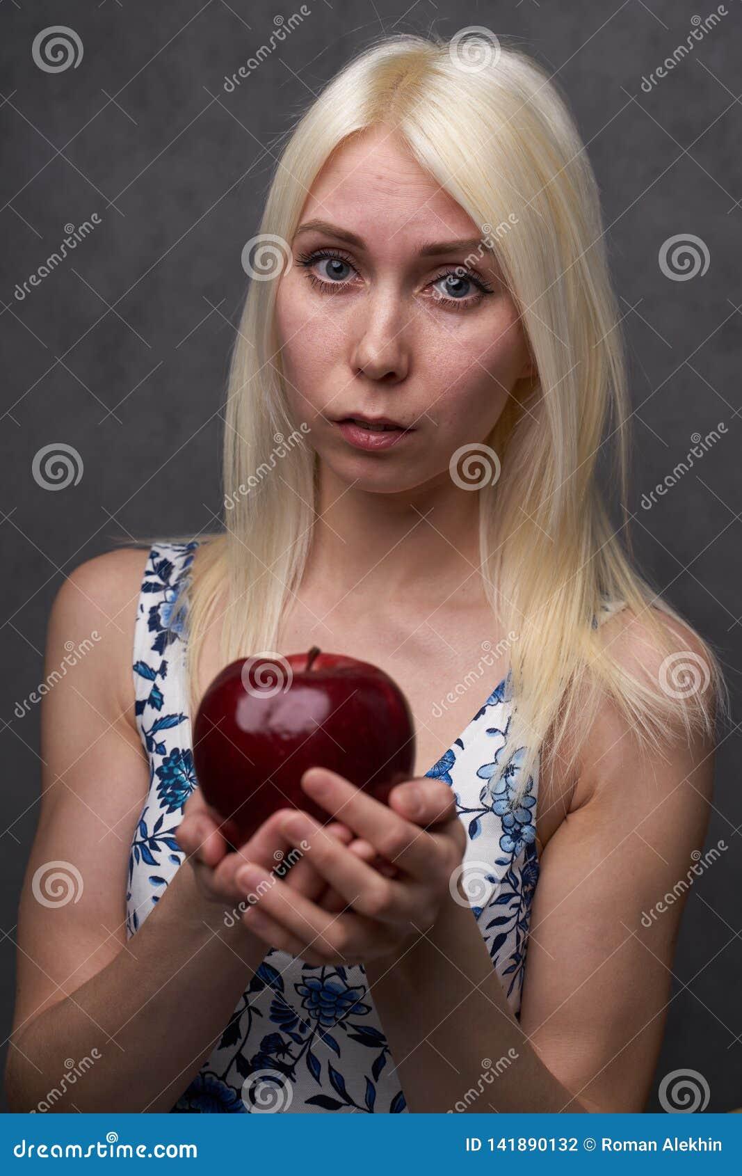 Härlig flicka i en trendig klänning med äpplet