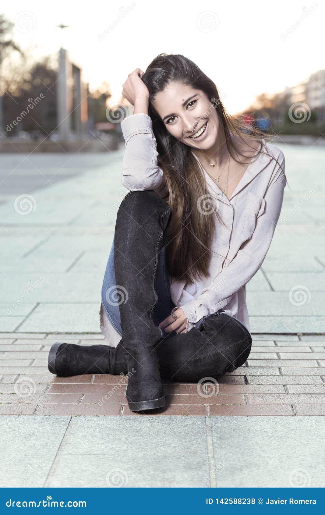 Härlig flicka i kängor som sitter på golvet