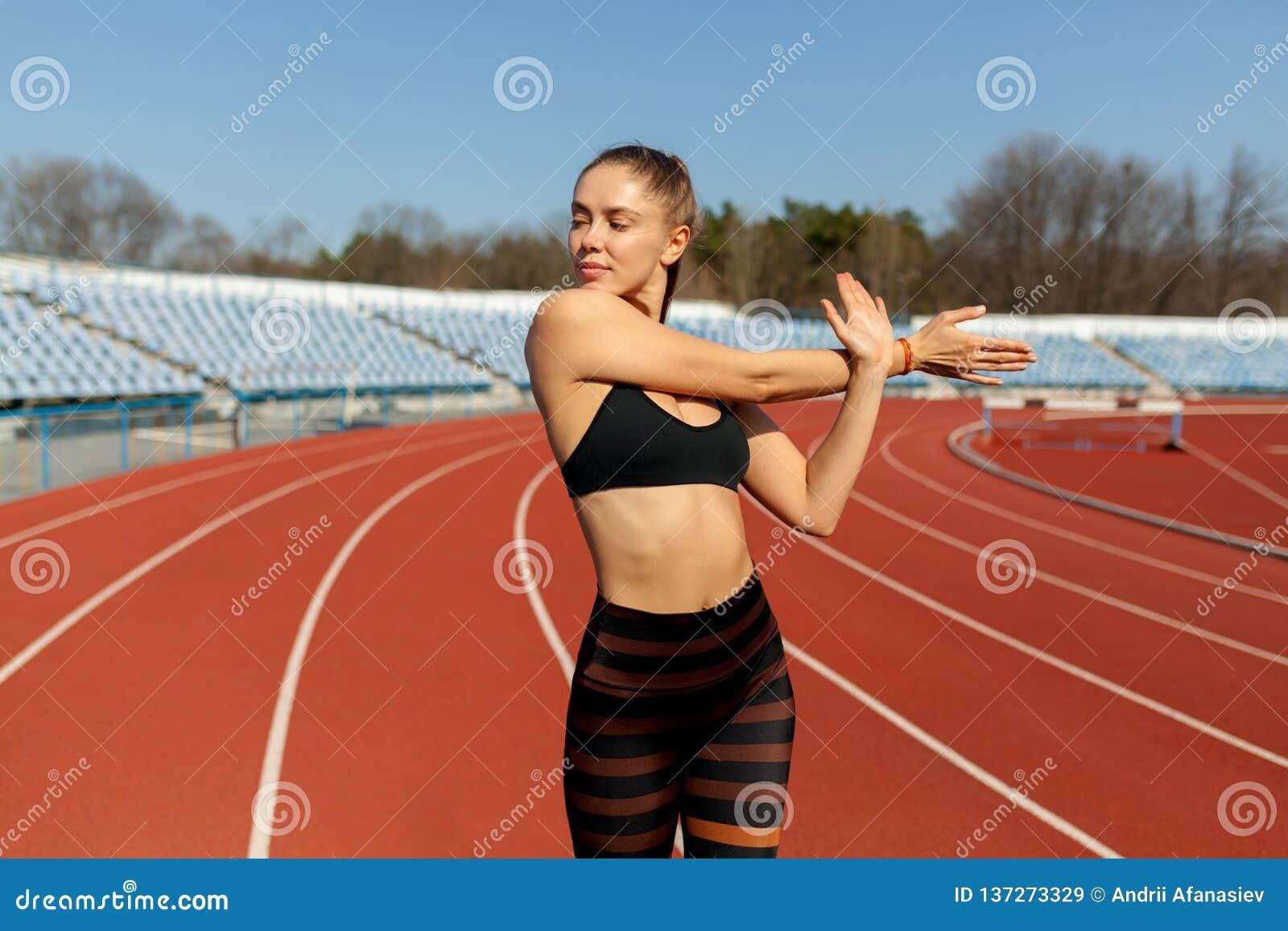 Härlig flicka, i sportswearanseende på det rinnande spåret och att förbereda sig att köra Morgonuppvärmning för övning
