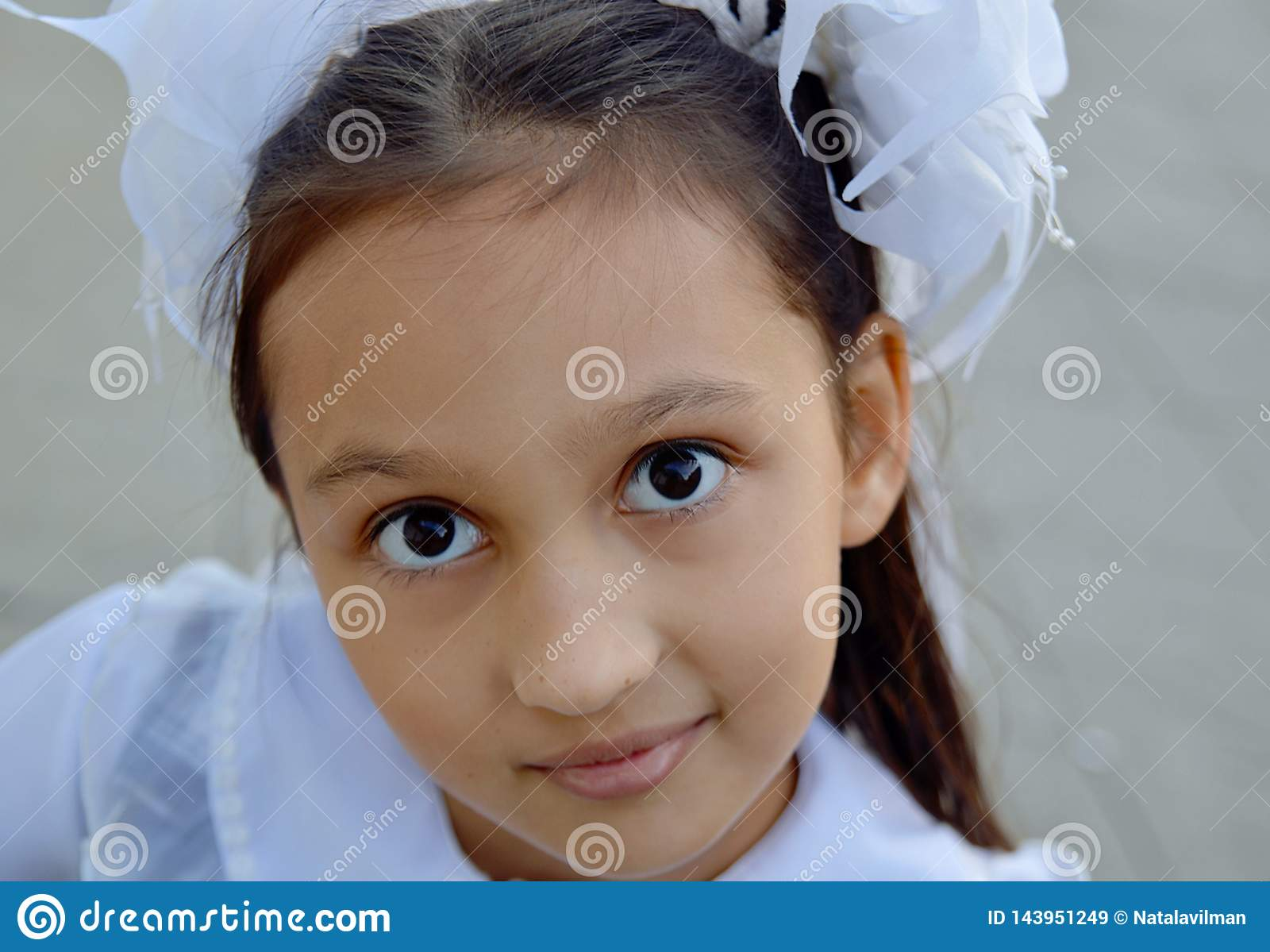 Härlig flicka med vita pilbågar, skolflickastående