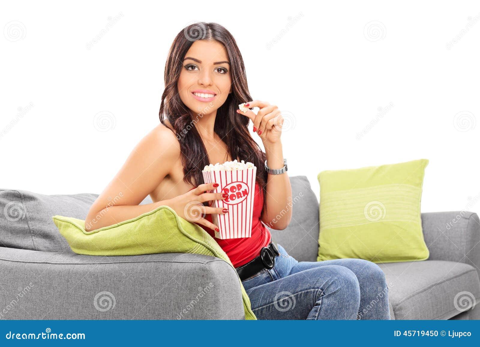 Härlig flicka som äter popcorn som placeras på en soffa