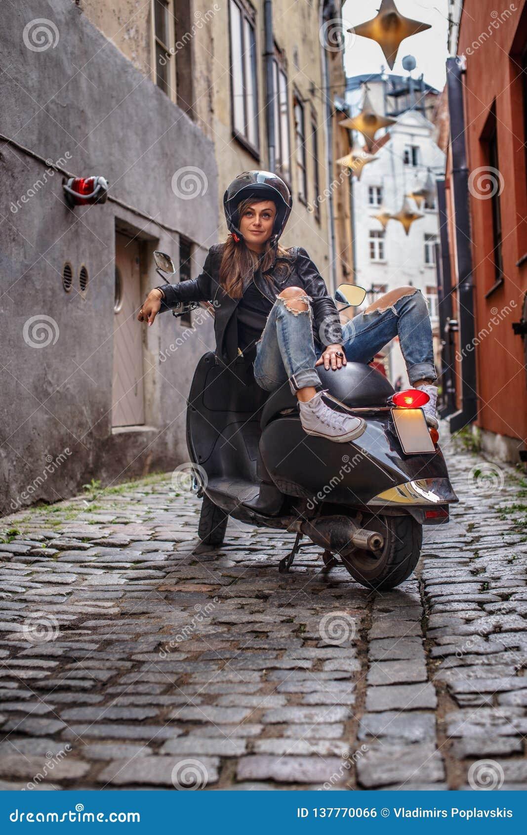 Härlig flicka som bär ett läderomslag och en riven sönder jeans som sitter på en svart klassisk sparkcykel på den gamla smala gat