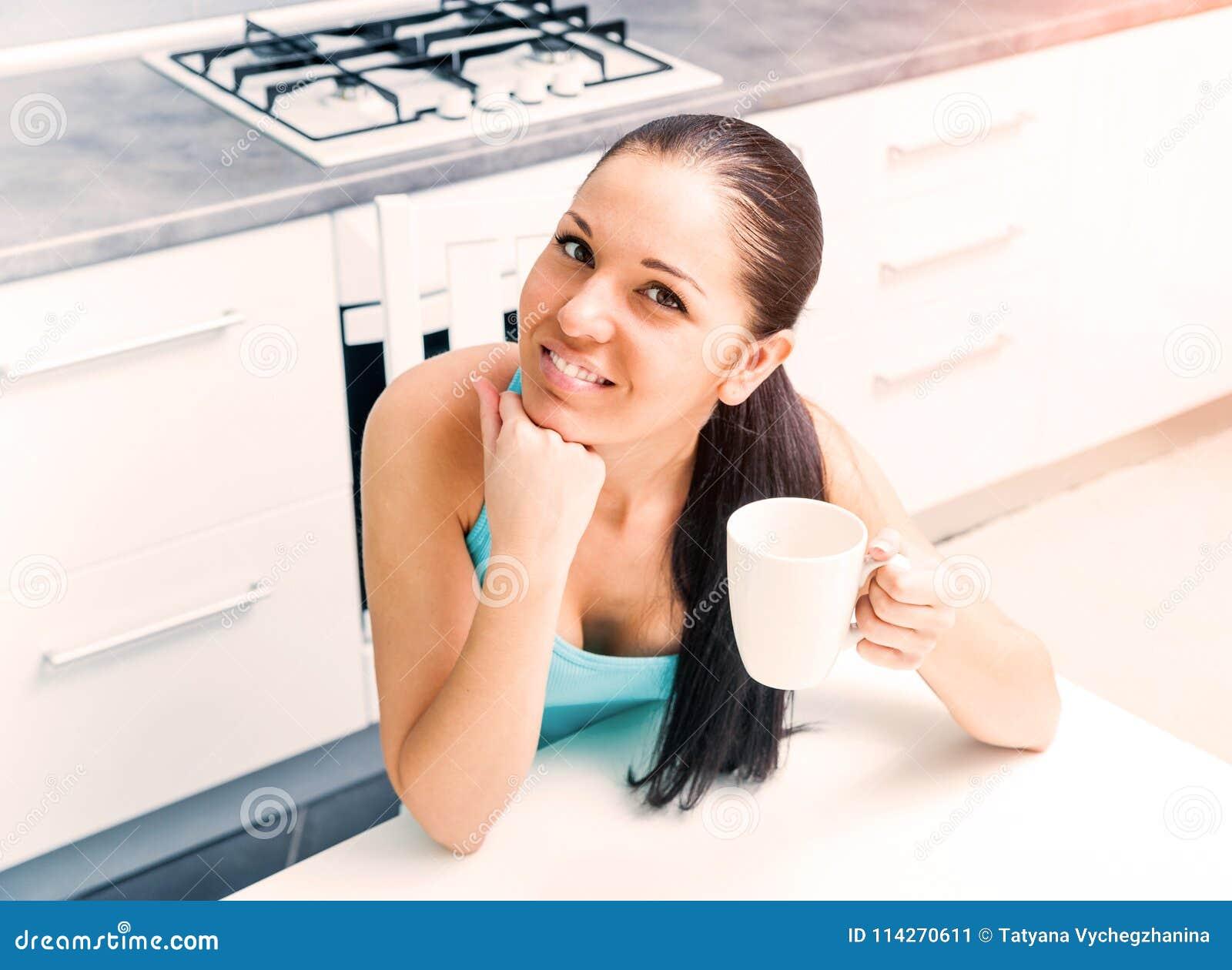 Härlig flicka som dricker te i köket