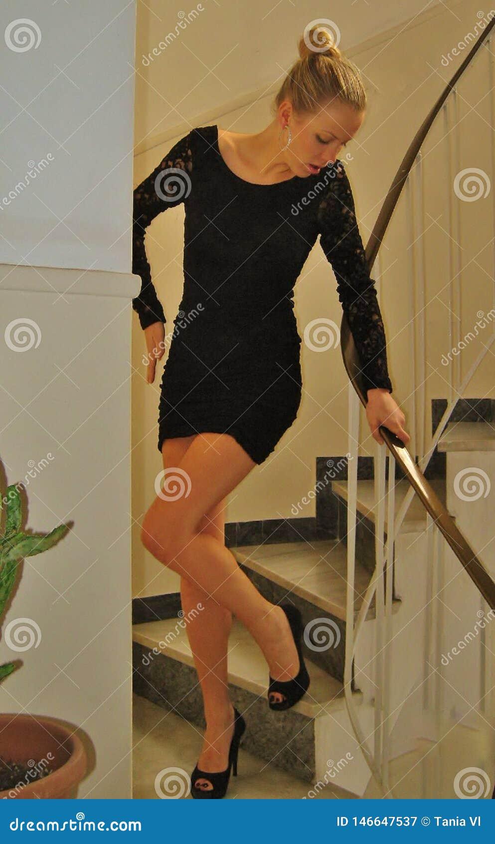 Härlig flicka som poserar i en svart klänning på momenten