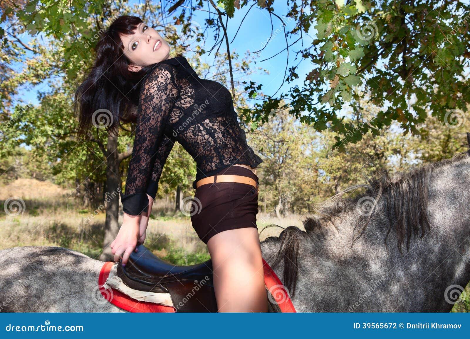 Härlig flicka som poserar i sadelhästen