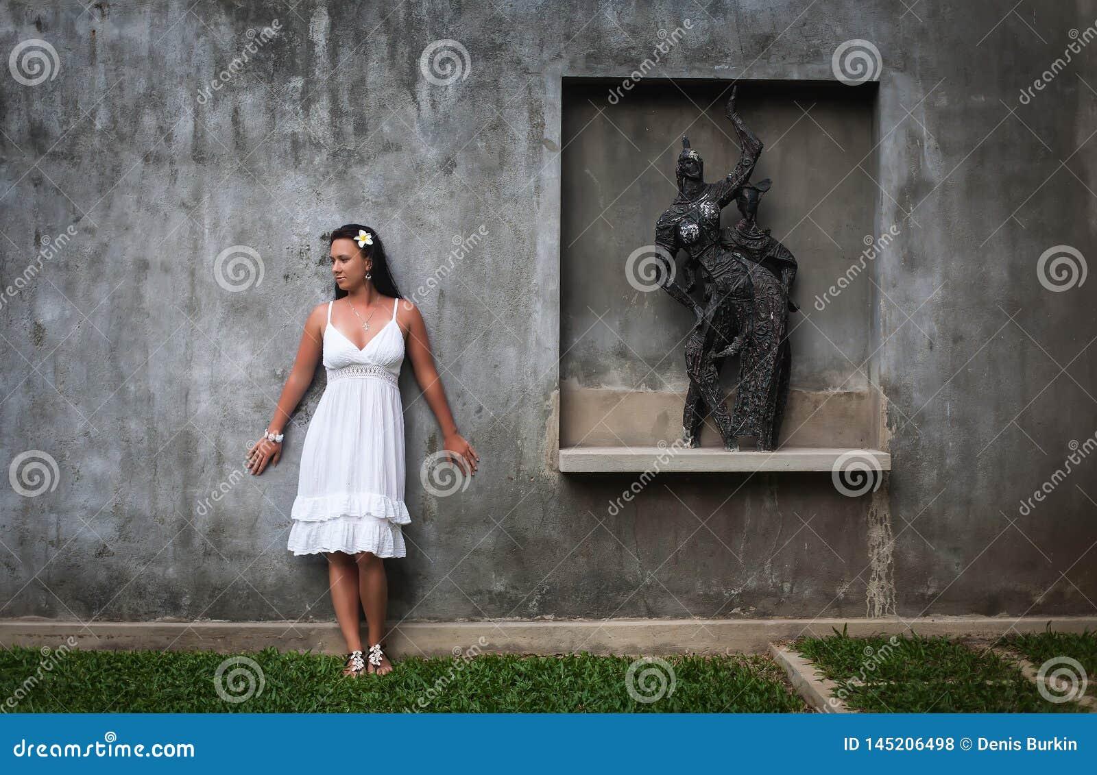 Härlig flicka som poserar nära statyn en kvinna i en vindstil flicka som poserar på plats