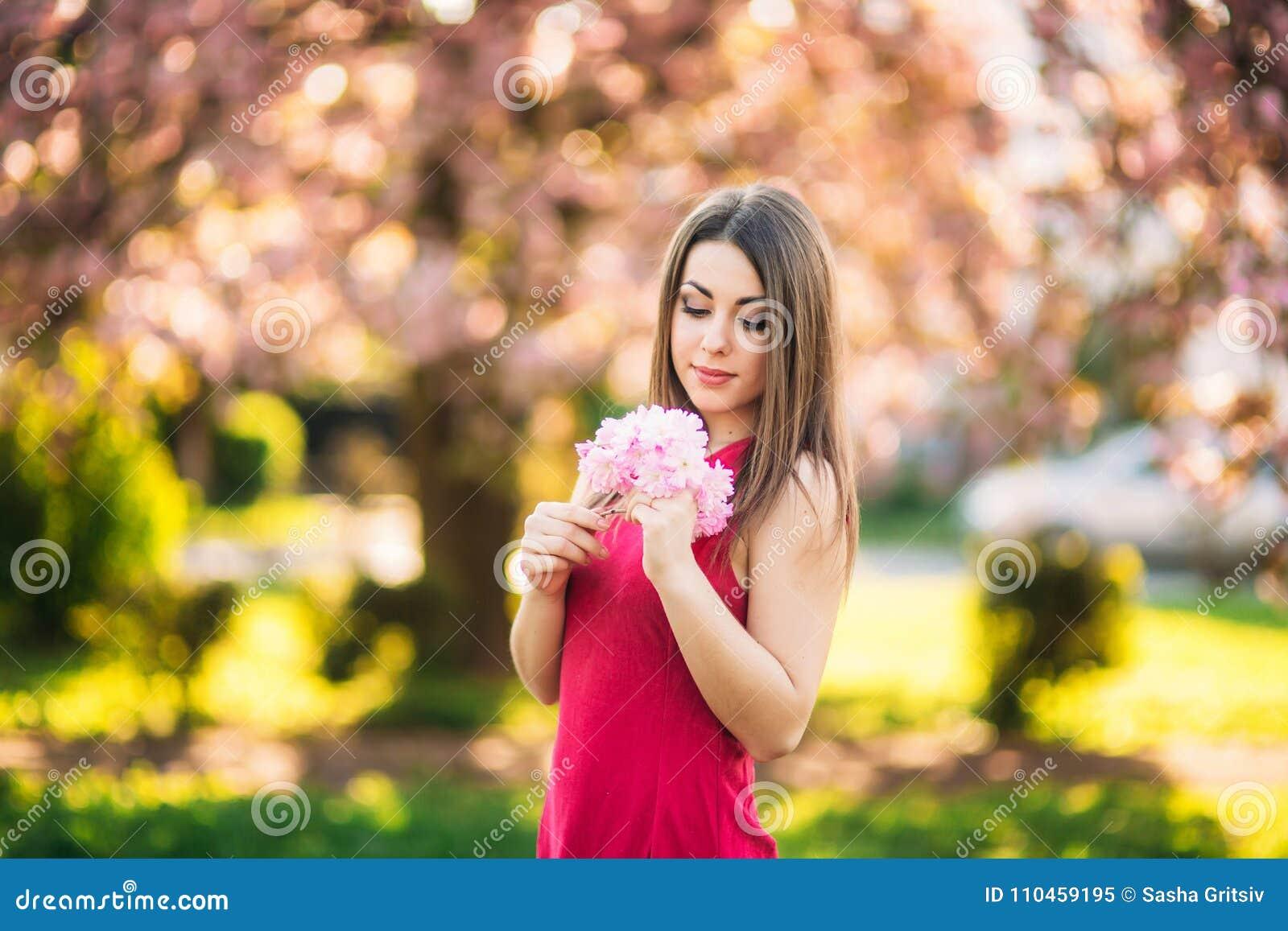 Härlig flicka som poserar till fotografen mot bakgrunden av blommande rosa träd Vår Sakura