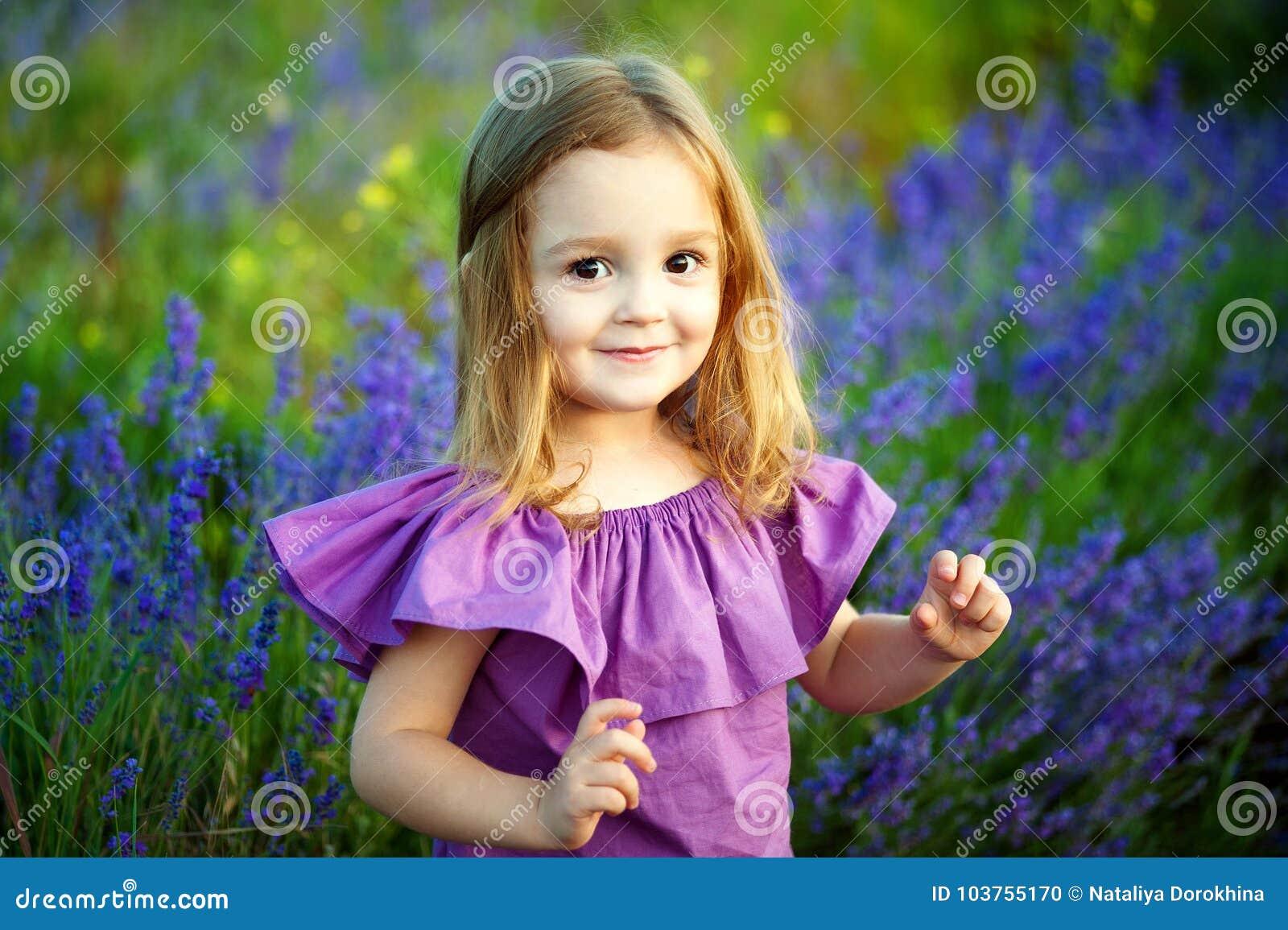 Härlig flicka som spelar i blommande lavendelblommafält Barnlek i vårblommor