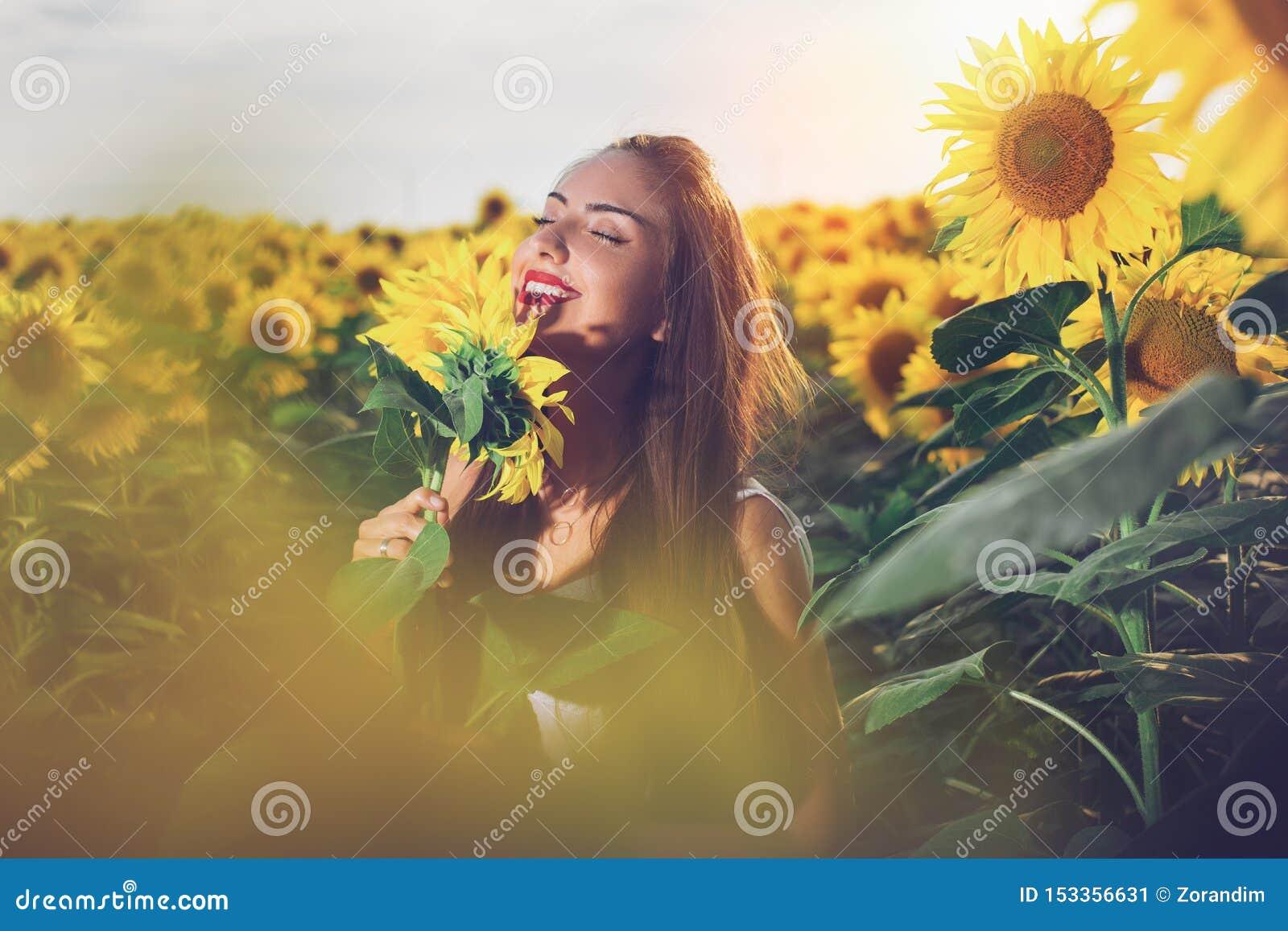 Härlig flicka som tycker om naturen på fältet av solrosor på solnedgången
