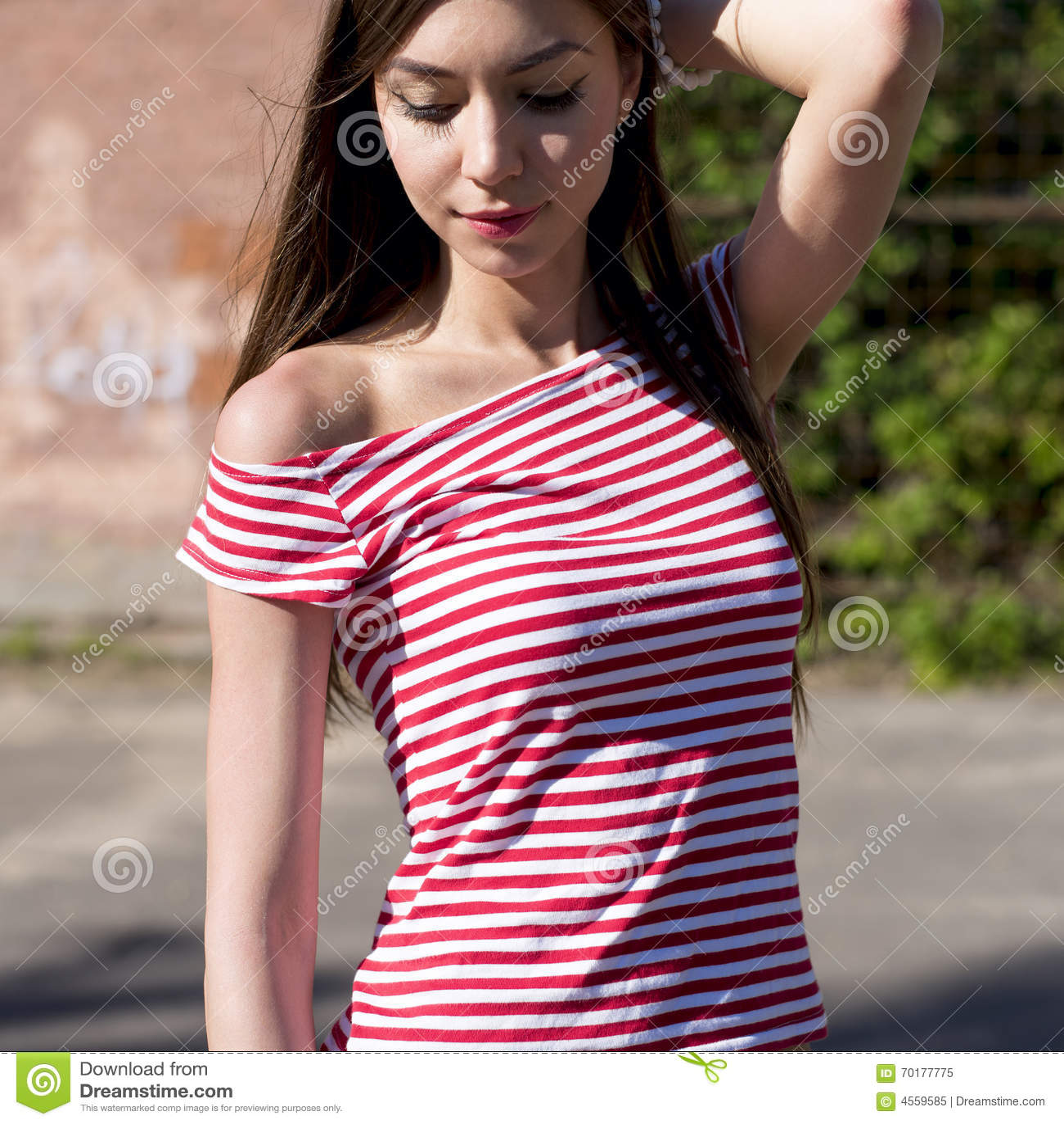 Härlig flicka, vilar utomhus som i vita kortslutningar för en ljus röd T-tröja, modestil