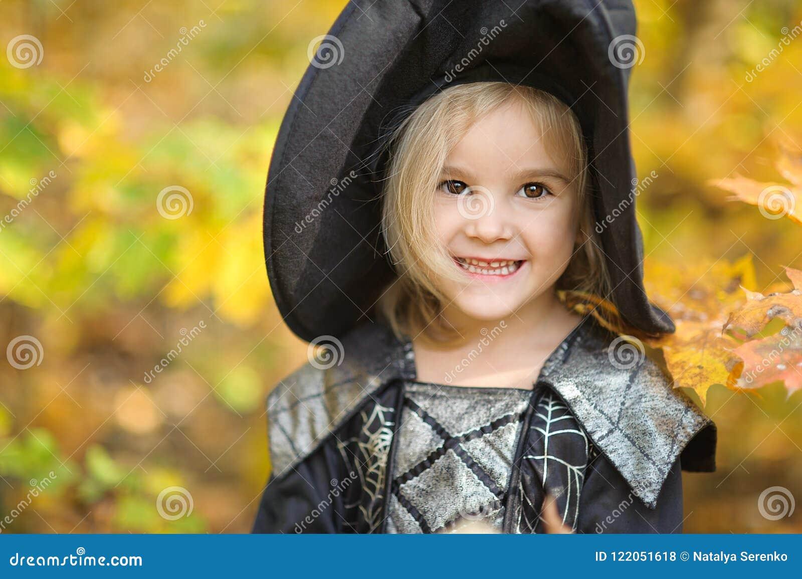 Härlig flickahäxa liten flicka som dräkten firar den utomhus- allhelgonaaftonen och har i en gyckel Ungetrick eller behandling