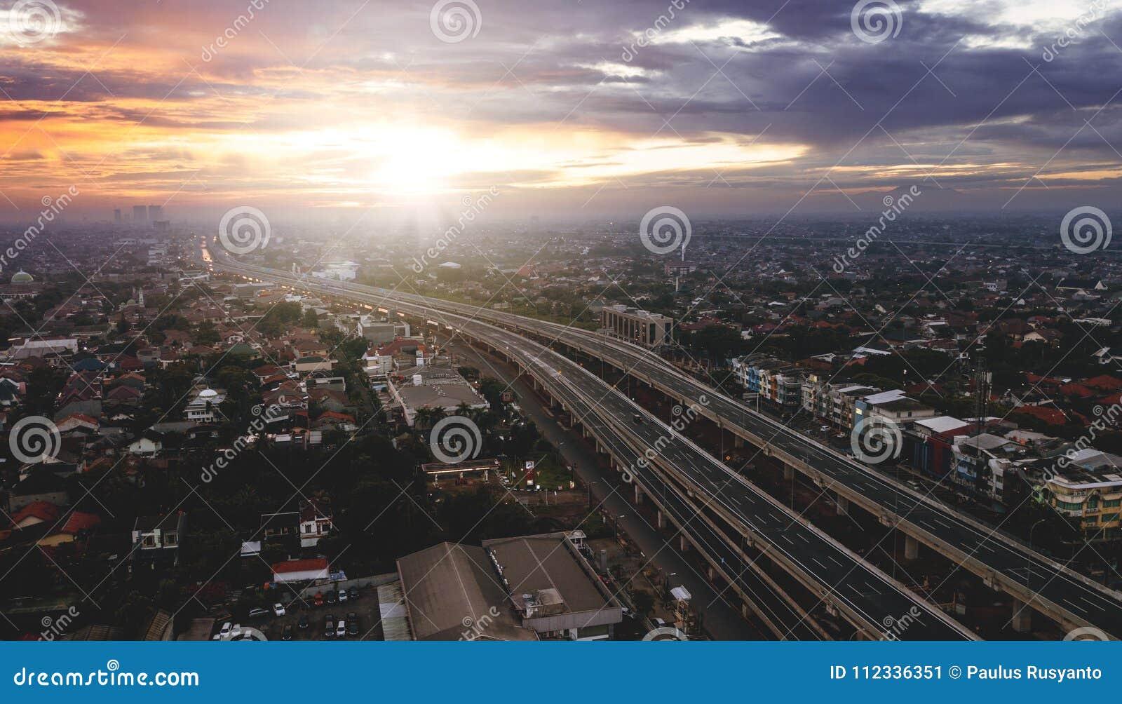 Härlig flyg- soluppgångsikt av avgiftvägen från Jakarta till Bekasi
