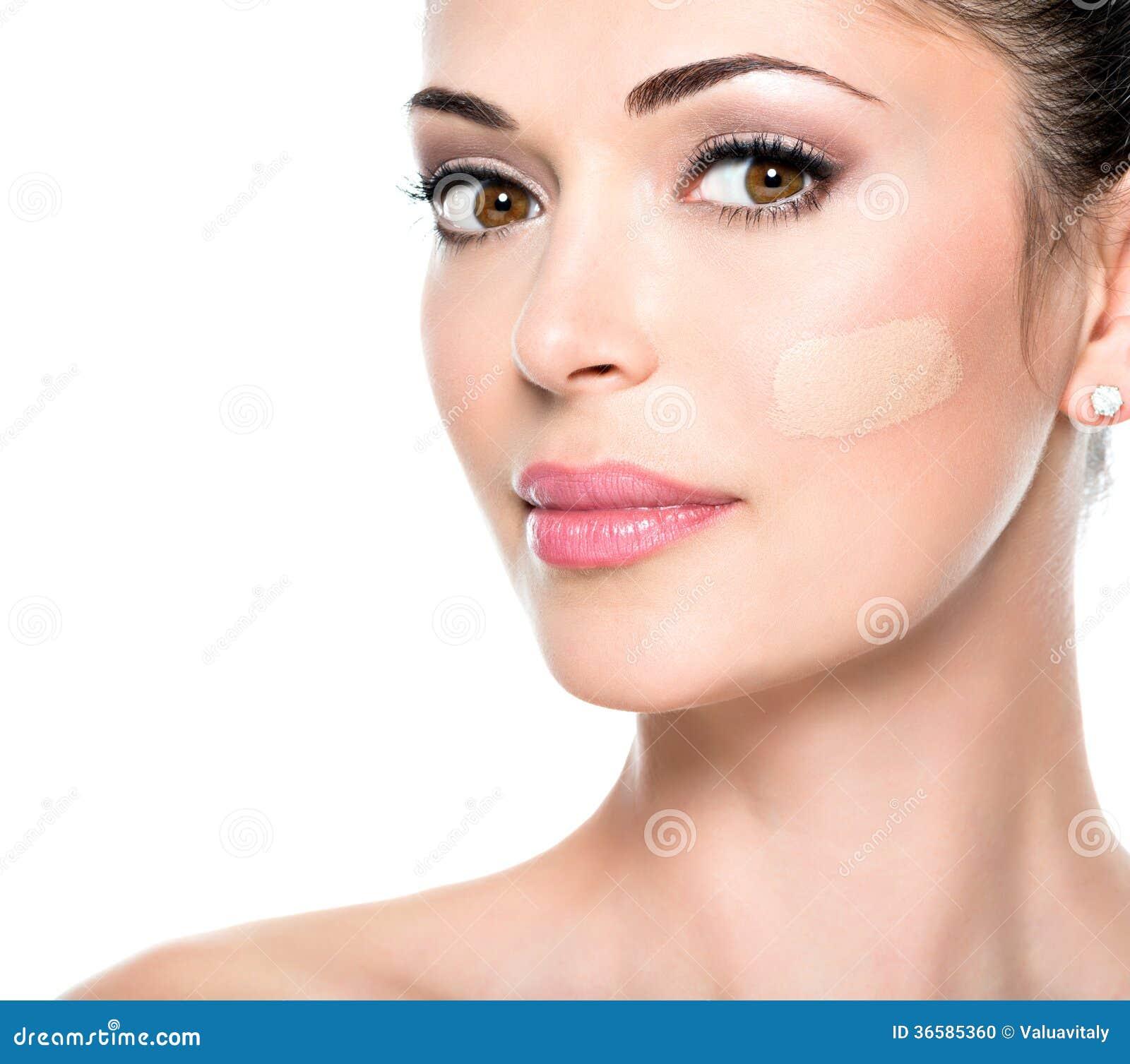 Härlig framsida av kvinnan med det kosmetiska fundamentet på en hud.
