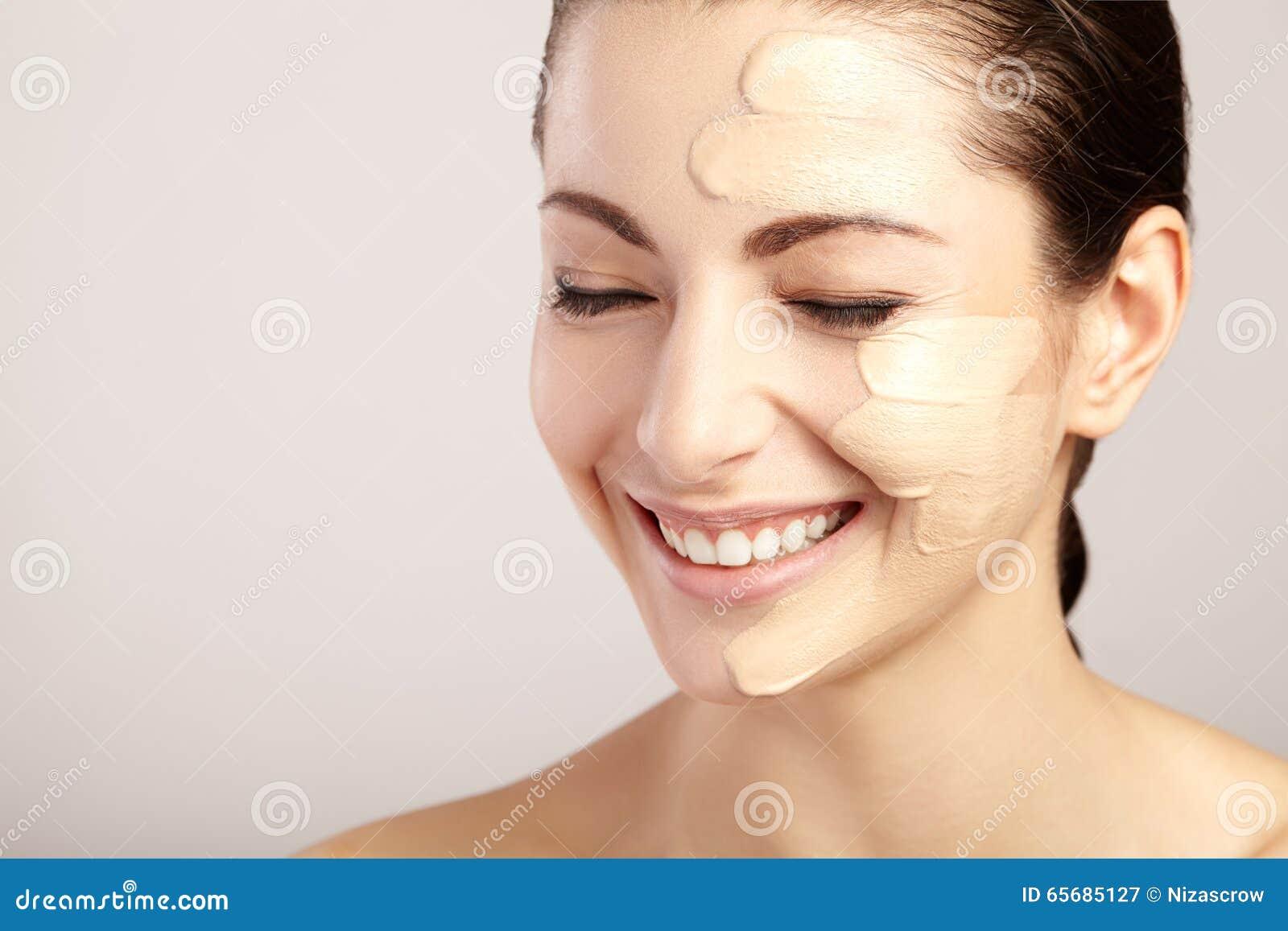 Härlig framsida av kvinnan med det kosmetiska fundamentet på hud