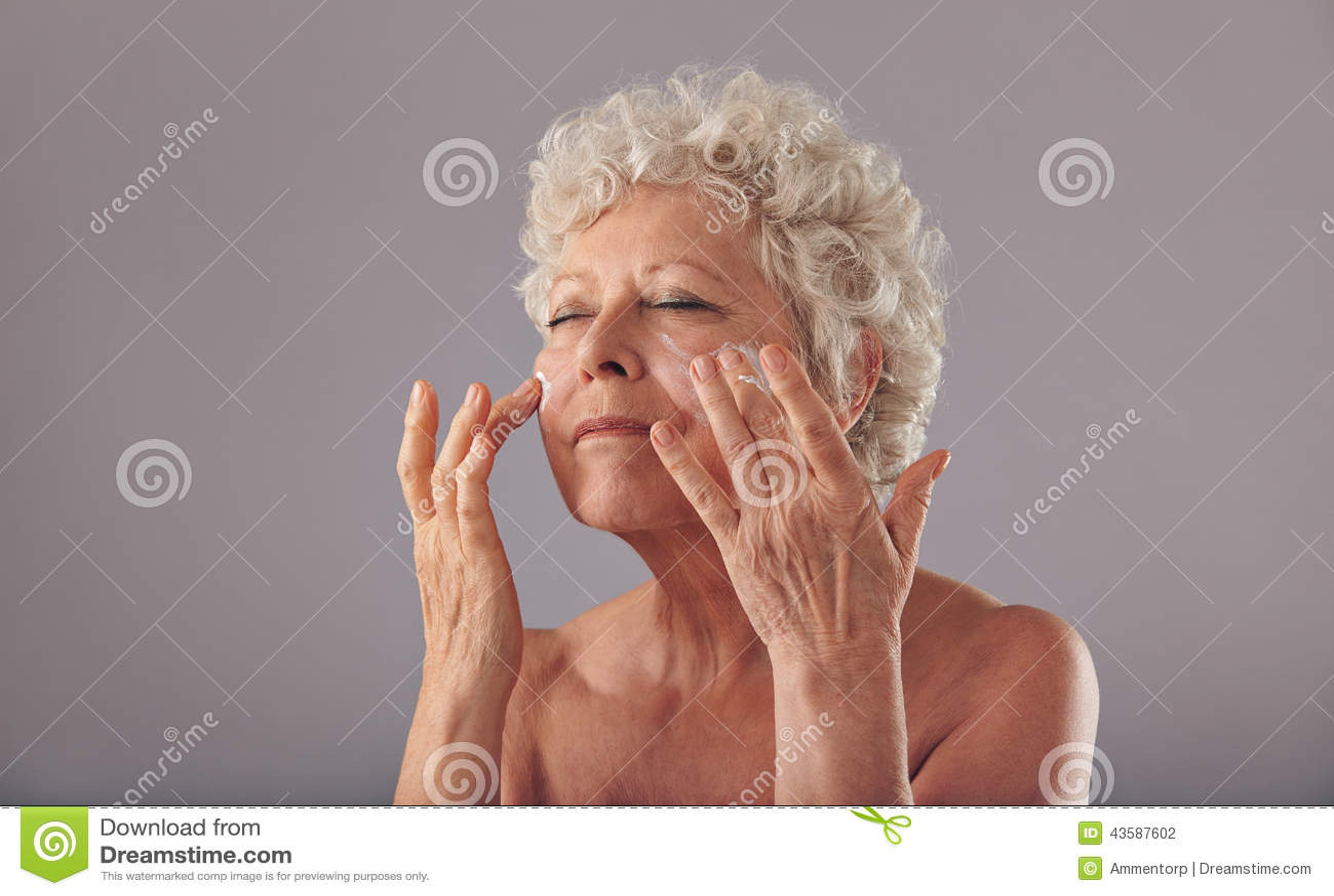 Härlig gammal kvinna som applicerar fuktighetsbevarande hudkräm på hennes framsida