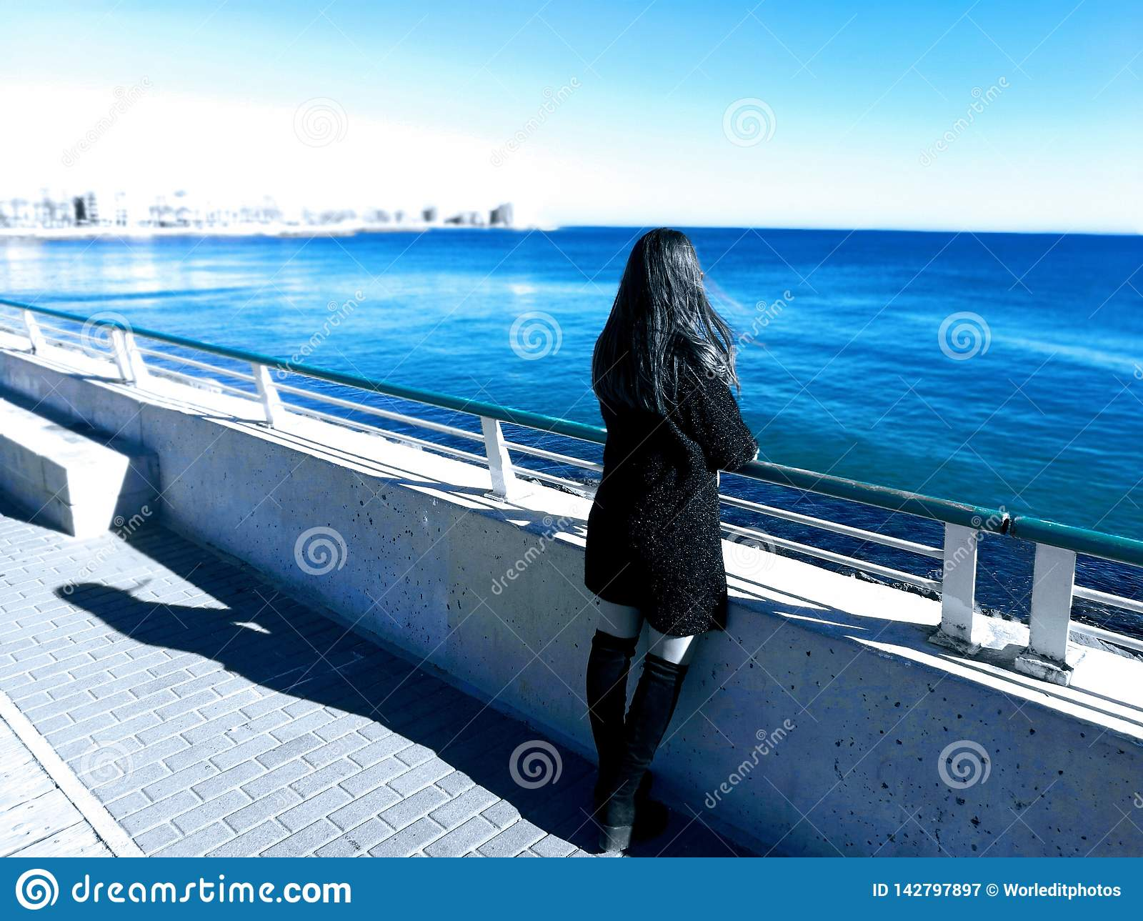 Härlig girlinsvartklänning som stirrar på stranden Begrepp för fantasivärld