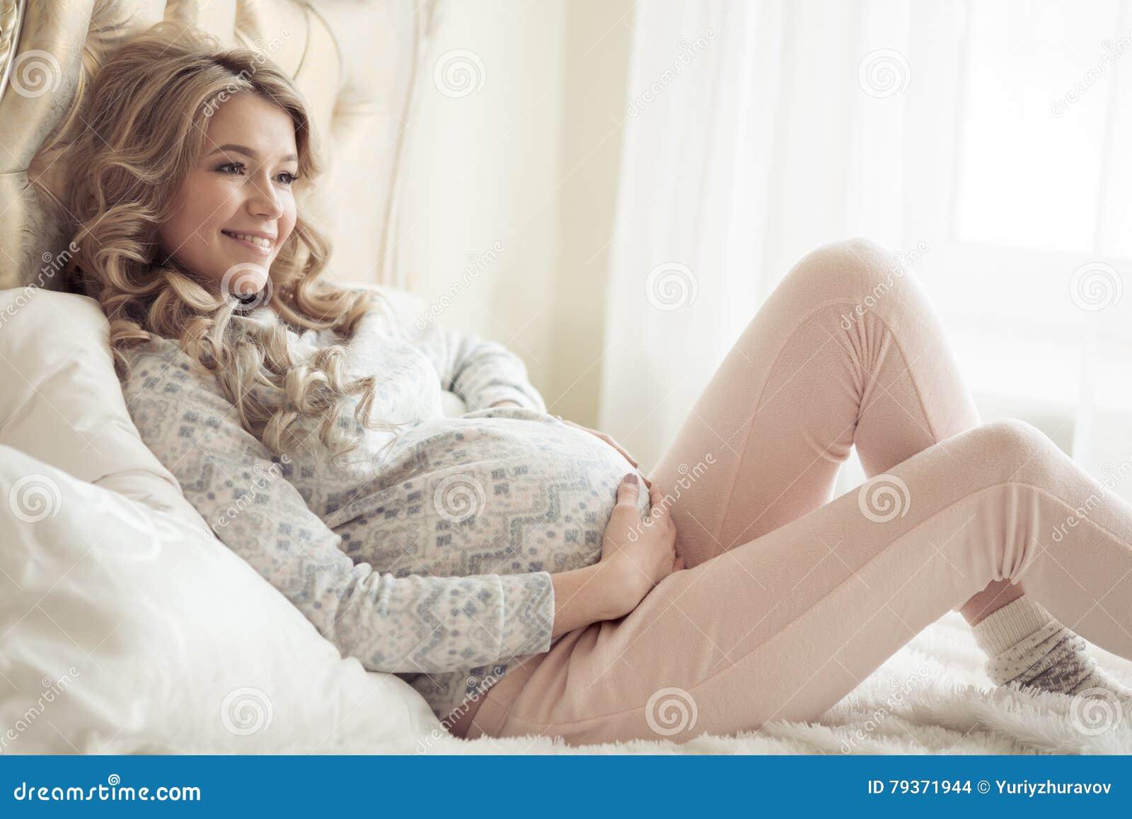 Härlig gravid kvinna i hemtrevlig kläder
