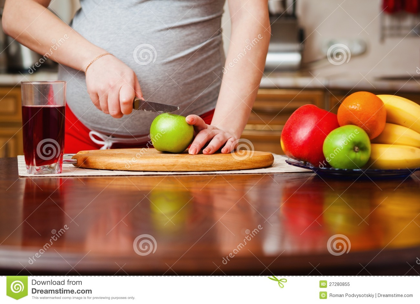 Härlig gravid kvinna på kök