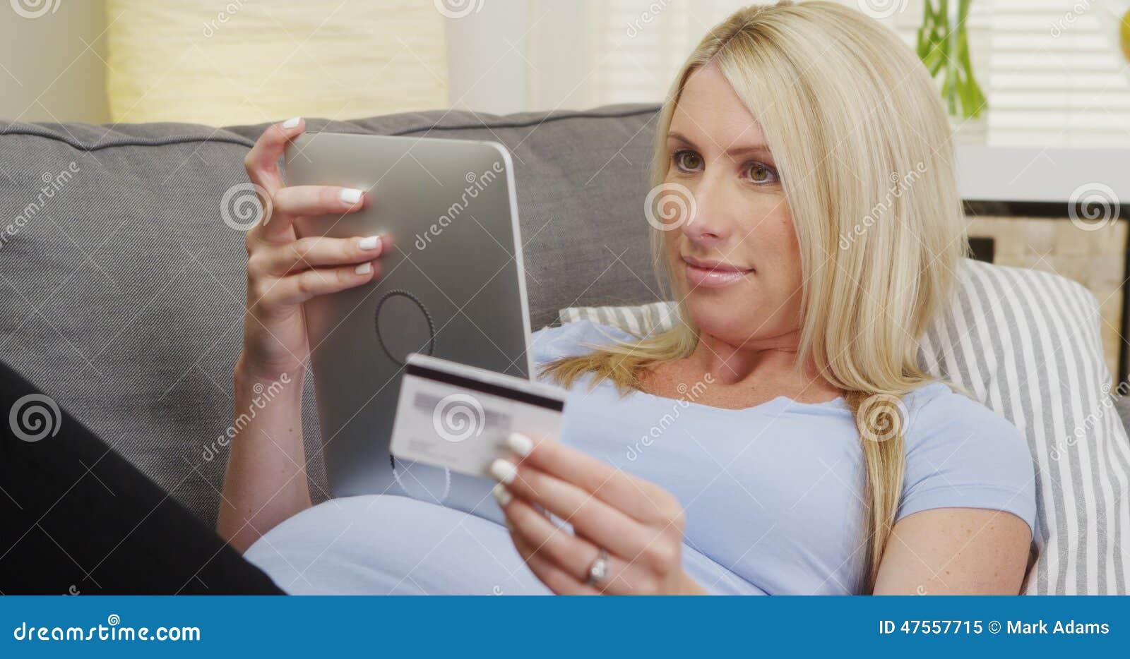 Härlig gravid kvinna som gör ett online-köp på minnestavlan