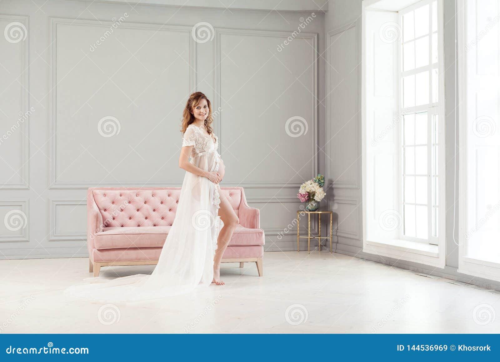 Härlig gravid ung kvinna i vit klänningpeignoir som står nära den rosa soffan som rymmer med förälskelse hennes buk
