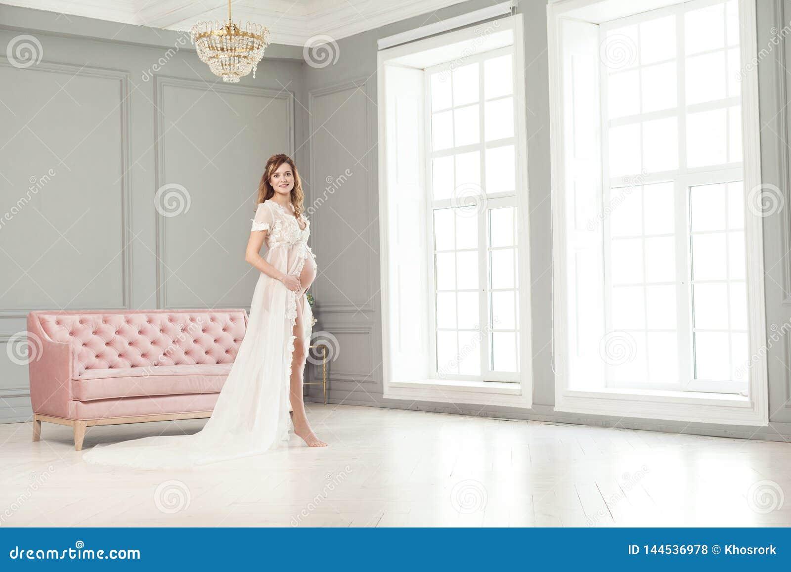 Härlig gravid ung kvinna i vit peignoir som står nära den rosa soffan som rymmer med förälskelse hennes buk