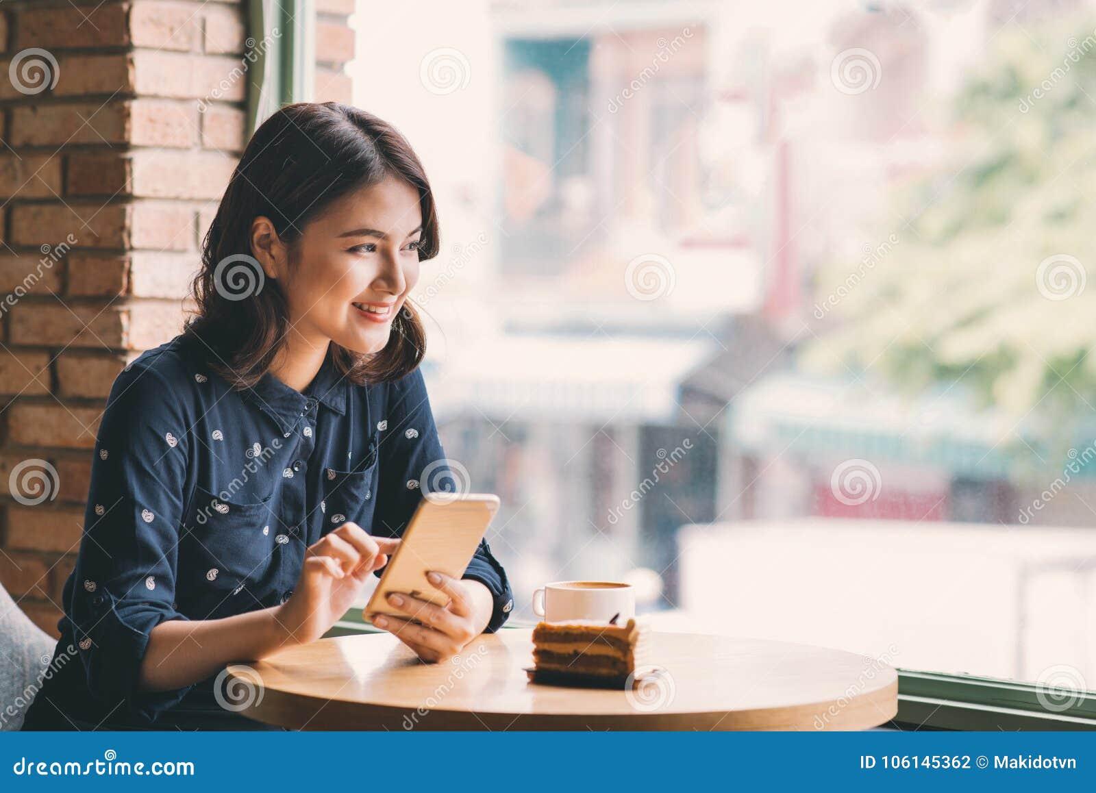 Härlig gullig asiatisk ung affärskvinna i kafét, genom att använda mobi