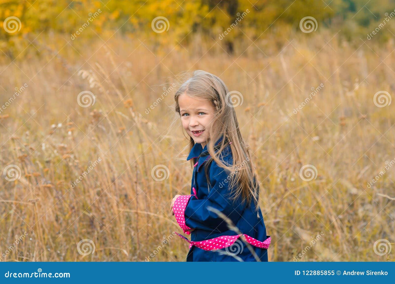 Härlig gullig flicka i kläder på bakgrund av autuen