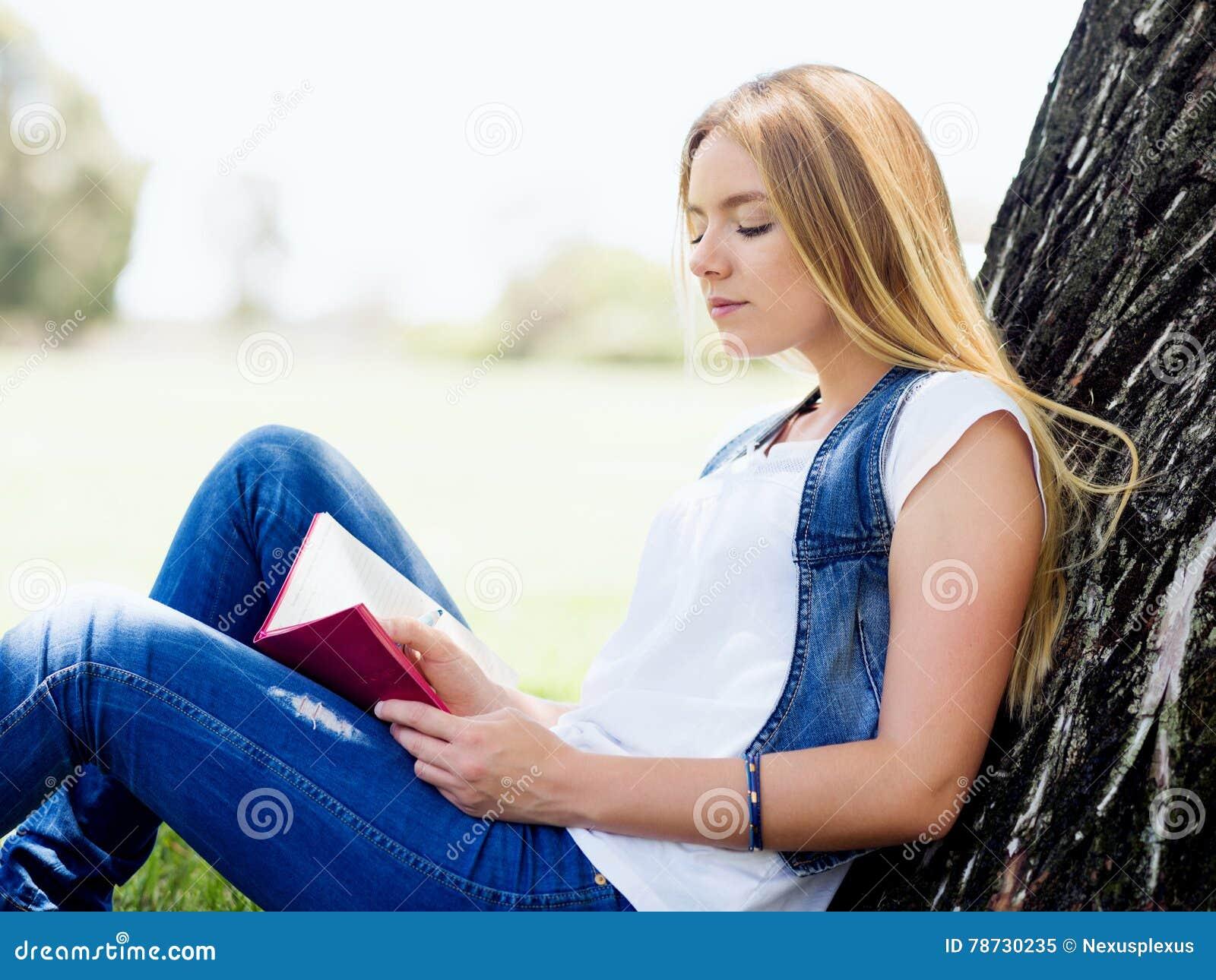 Härlig handstil för ung kvinna i hennes dagbok utomhus