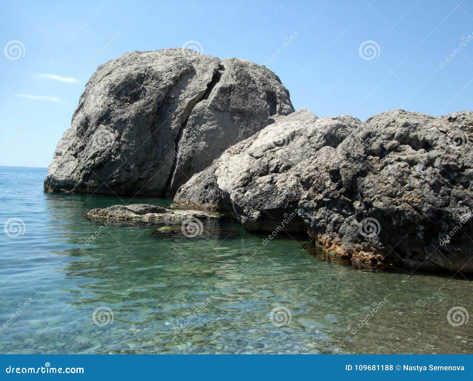 Härlig havsstrand som förbiser det blåa vattnet och de stora stenarna Black Sea crimea