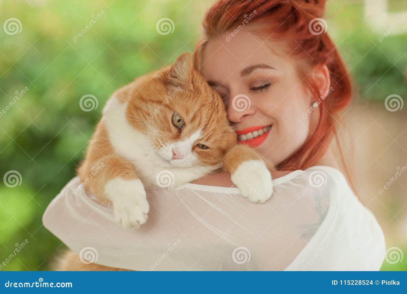 Härlig kel för ung kvinna med den gulliga röda katten