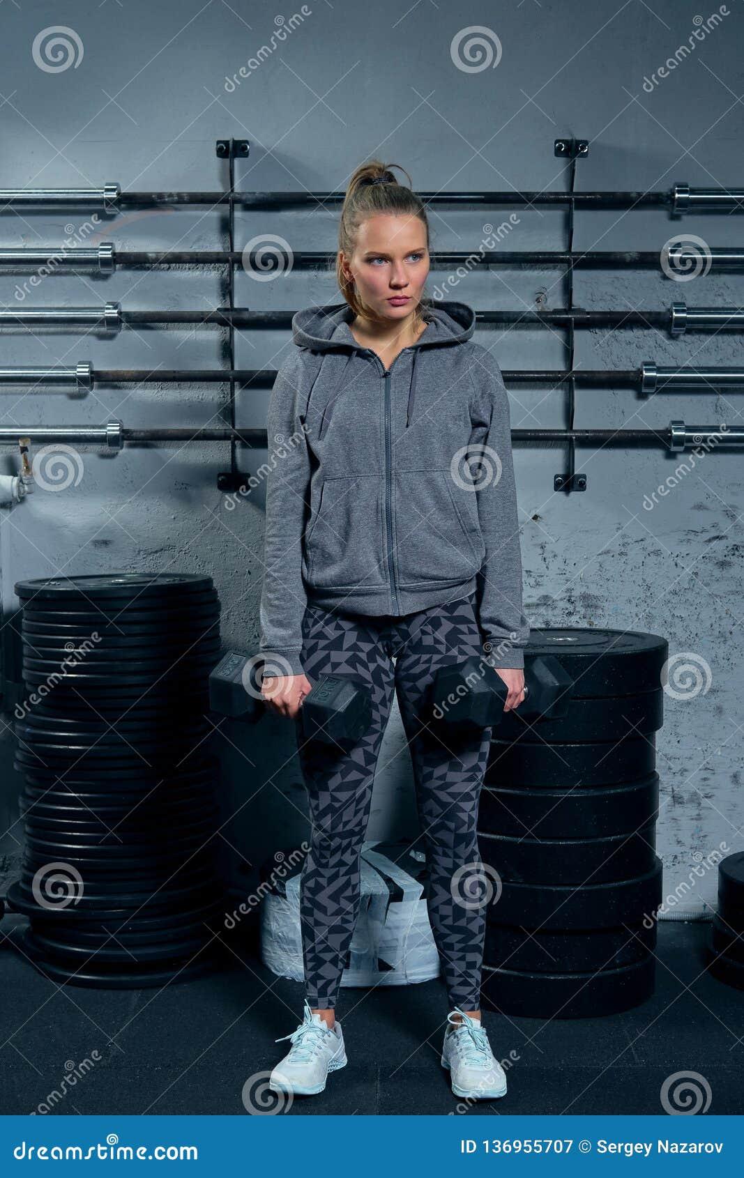 Härlig konditioninstruktör för ung kvinna som bär en sportdräkt som gör utfall för en övning med hantlar på en grå färg