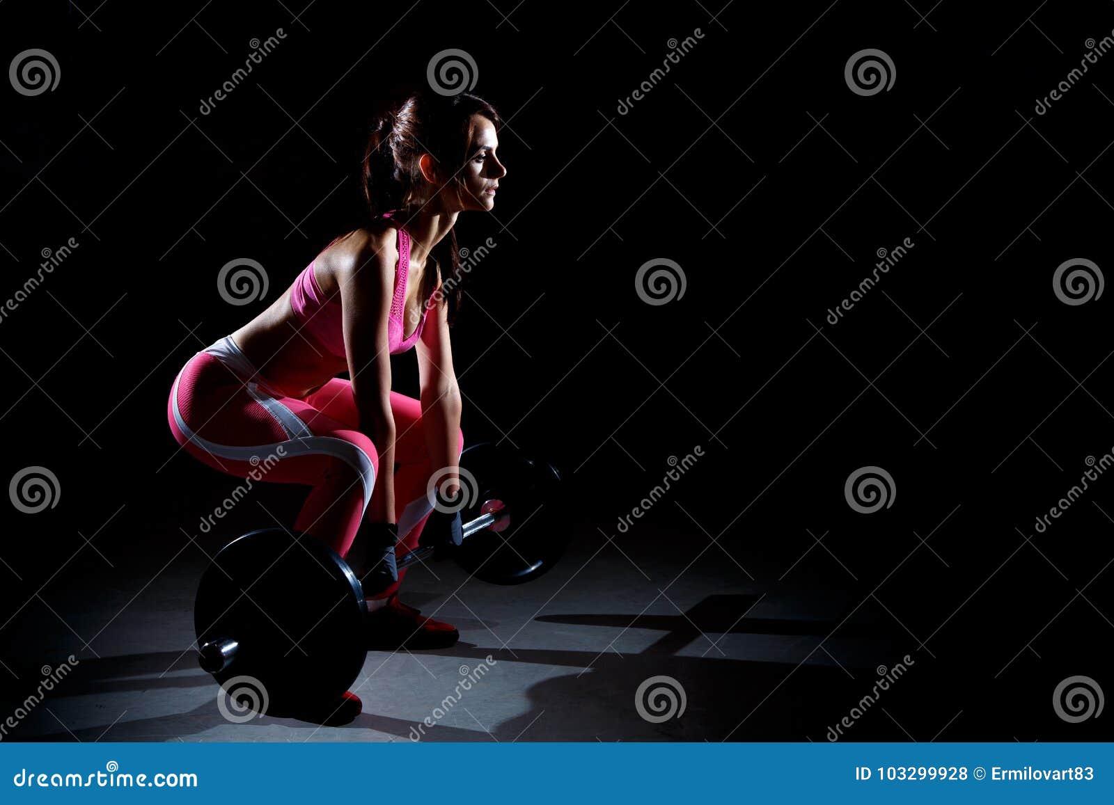 Härlig konditionkvinna som gör squats med en skivstång Kontur av sportkvinnan på en svart bakgrund