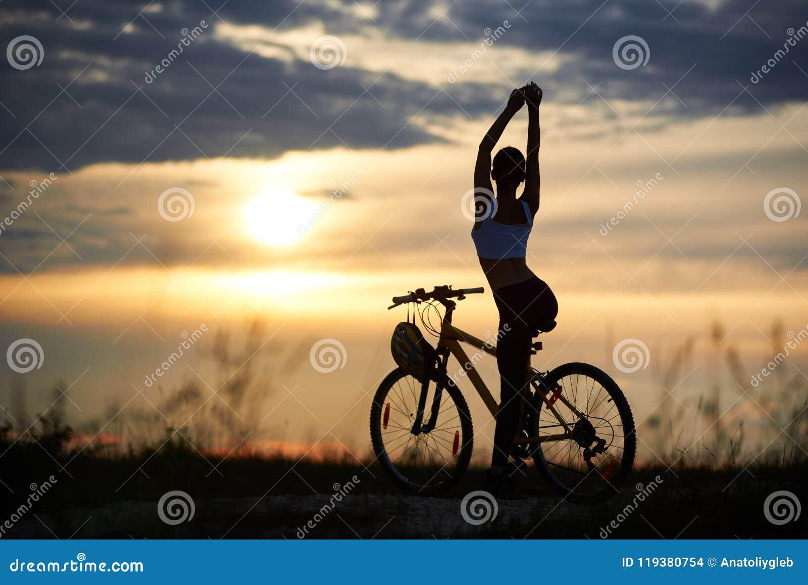 Härlig kontur för bakre sikt av den perfekta kroppkvinnlign mot bakgrundsaftonhimlen med inställningssolen