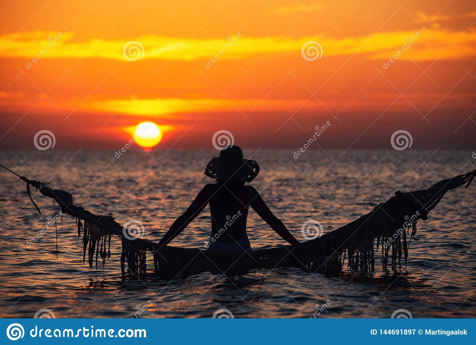 Härlig kontur för ung kvinna med gunga som poserar i havet på solnedgången, maldivian romantiskt landskap