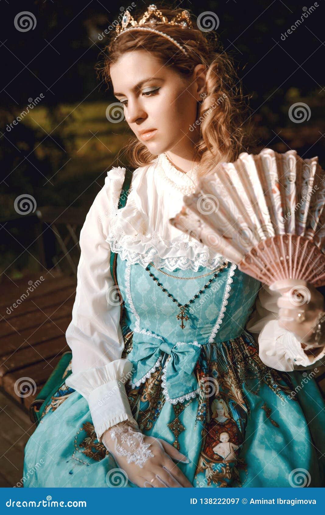 Härlig kvinna i blå klänning för tappning med fanen i kronadiadem Viktoriansk dam elegantt