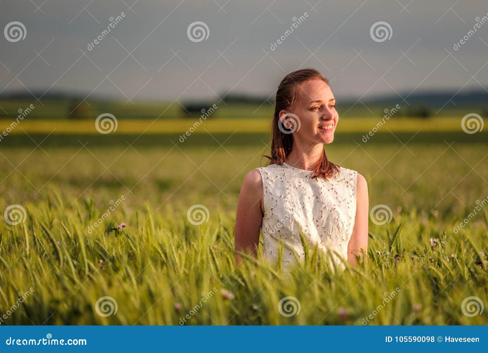 Härlig kvinna i den vita klänningen på grönt vetefält
