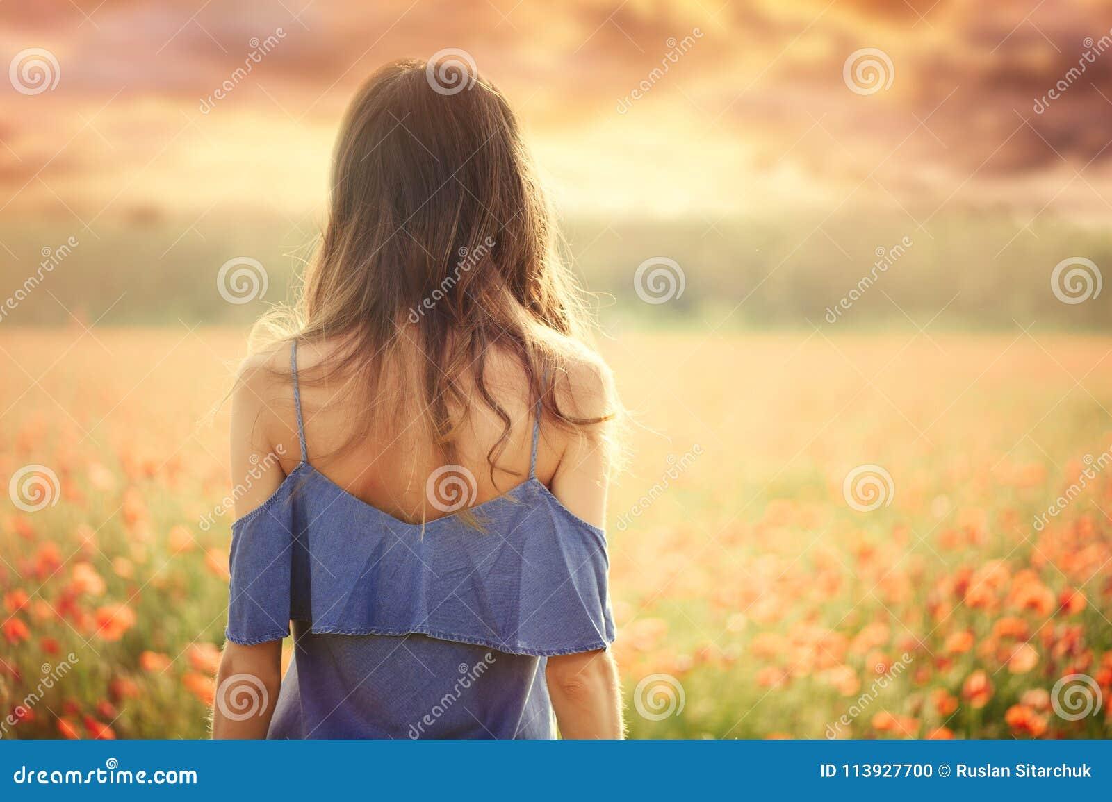 Härlig kvinna i en blå klänning i ett vetefält på solnedgången från den tillbaka varma toningen, lycka och en sund livsstil