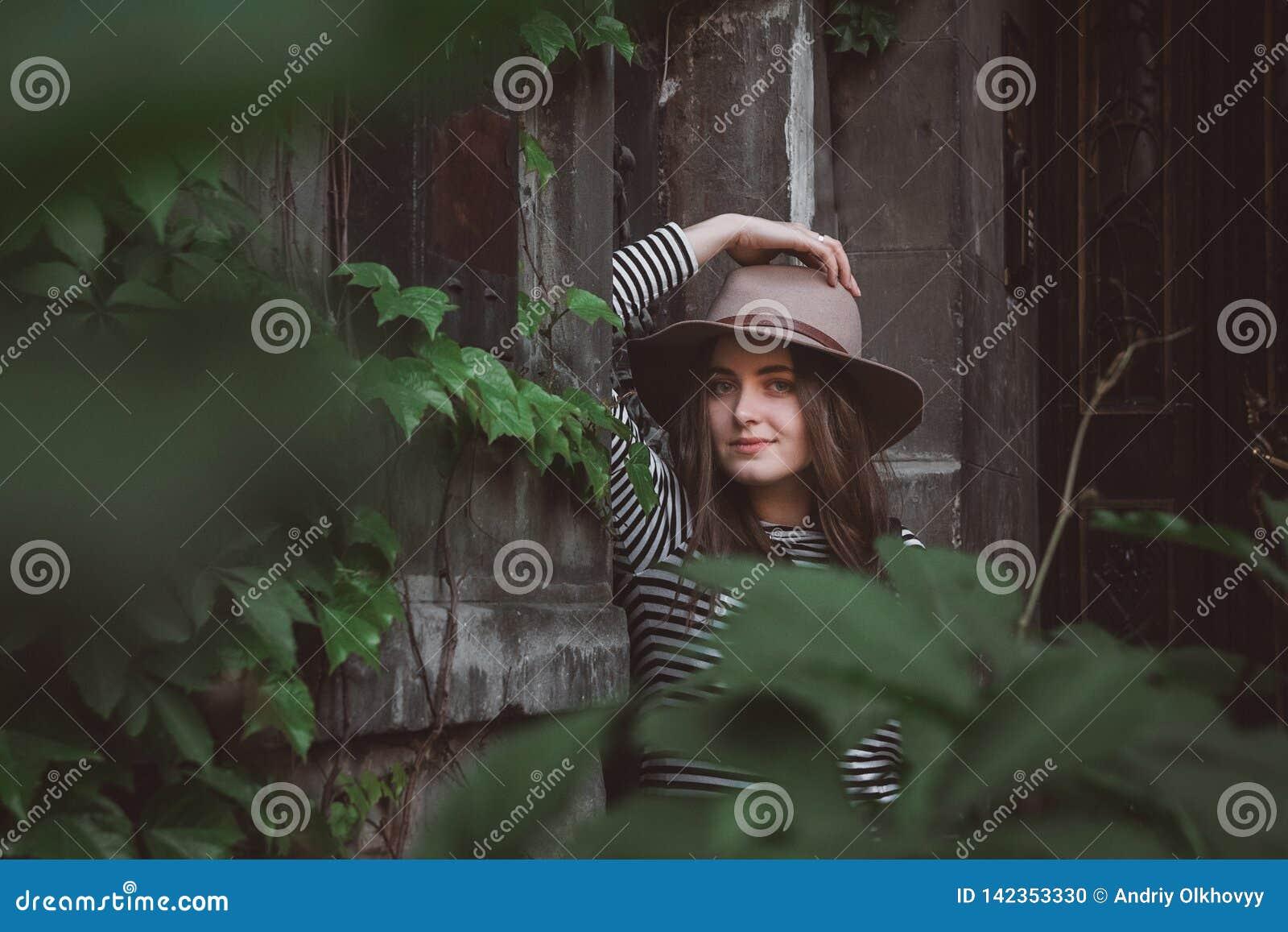 Härlig kvinna i en randig skjorta som rymmer hennes hatt och ser en kamera