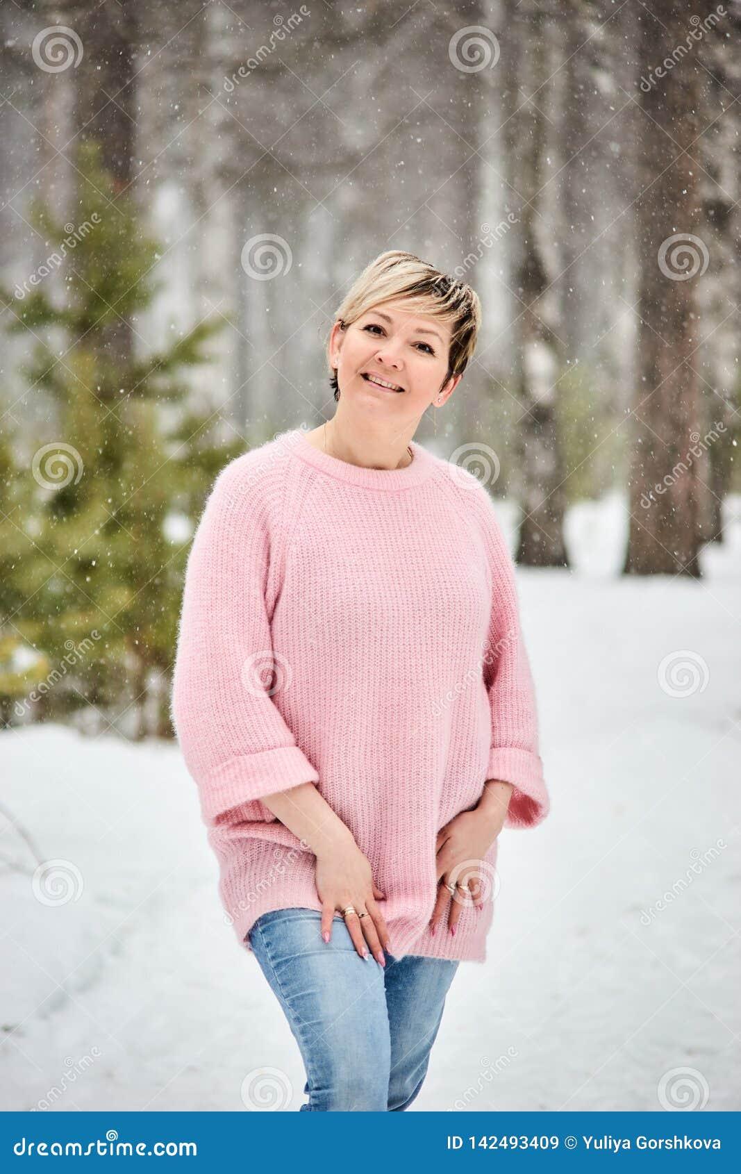 Härlig kvinna i vinterskogsnöfallet