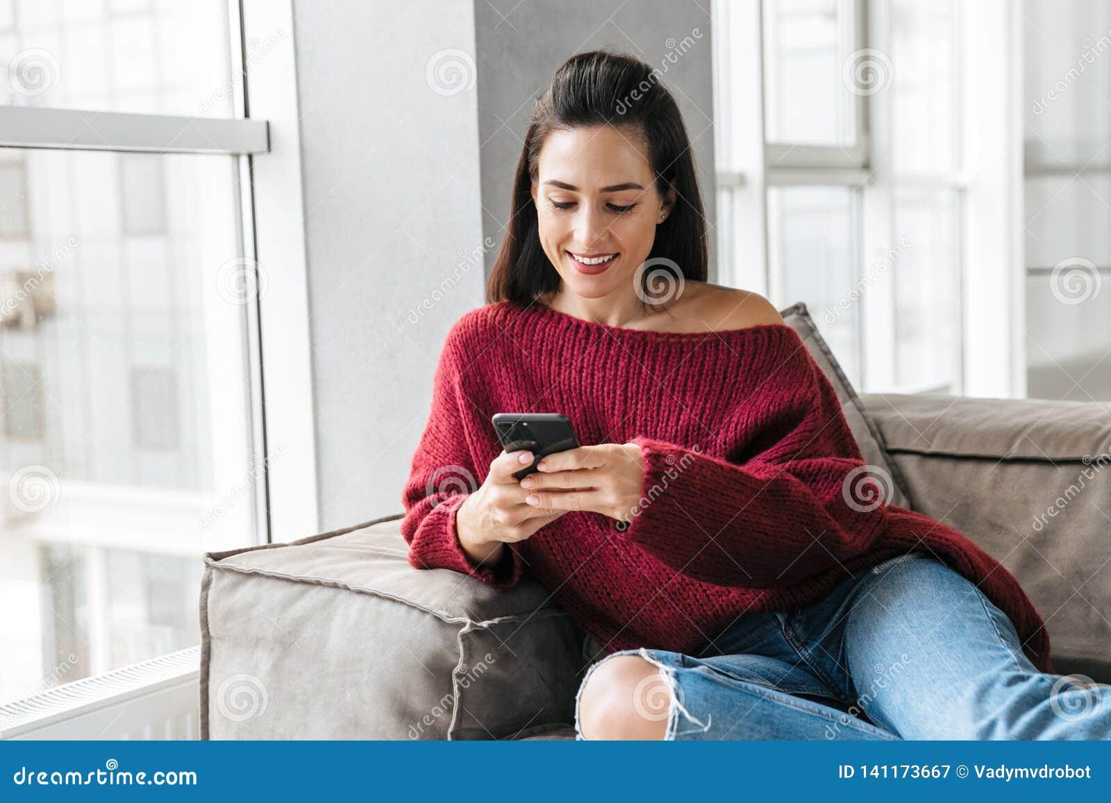 Härlig kvinna inomhus i hem på soffan genom att använda mobiltelefonen