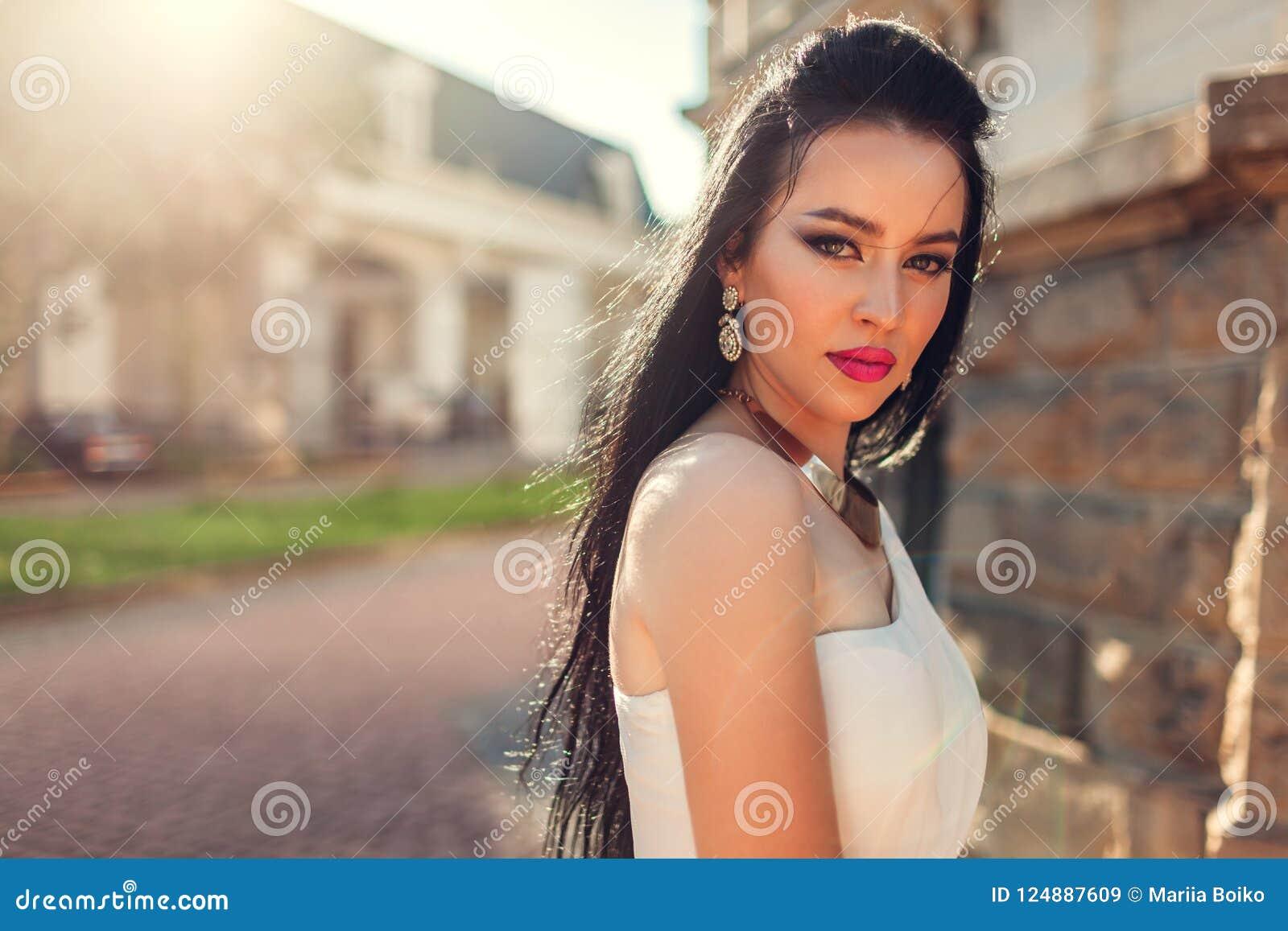 Härlig kvinna med den bärande vita bröllopsklänningen för långt hår utomhus Skönhetmodemodell med smycken och makeup
