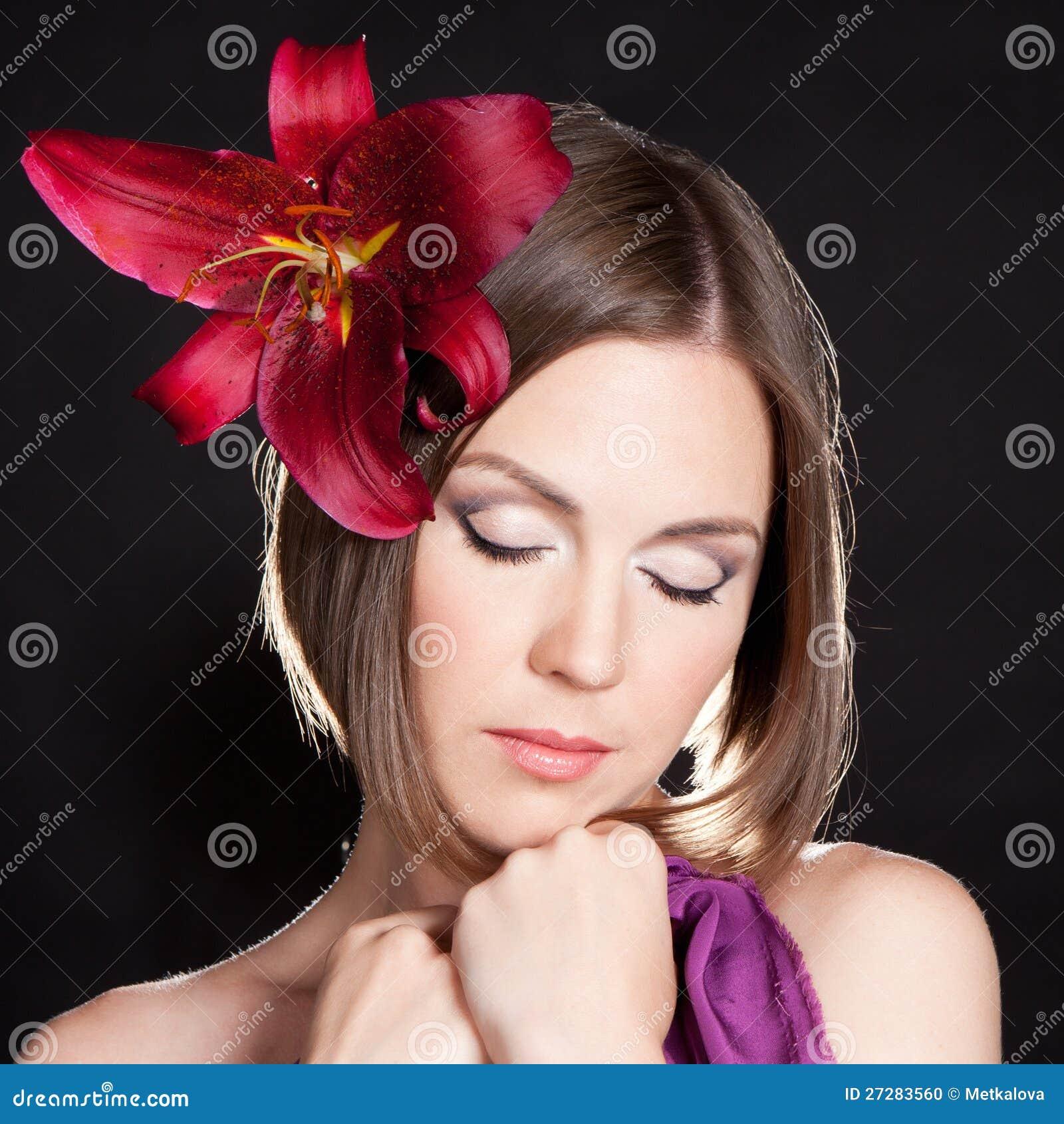 Härlig kvinna med den röda blomman