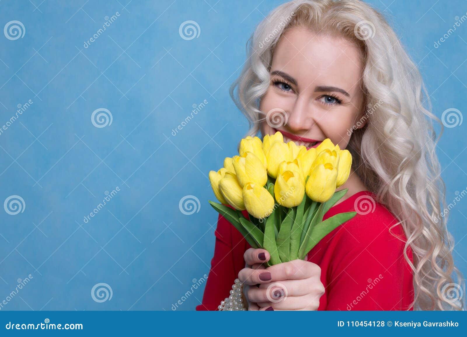 Härlig kvinna med en bukett av tulpan mot barn för fjäder för bakgrundsbegreppsblomma vitt gult