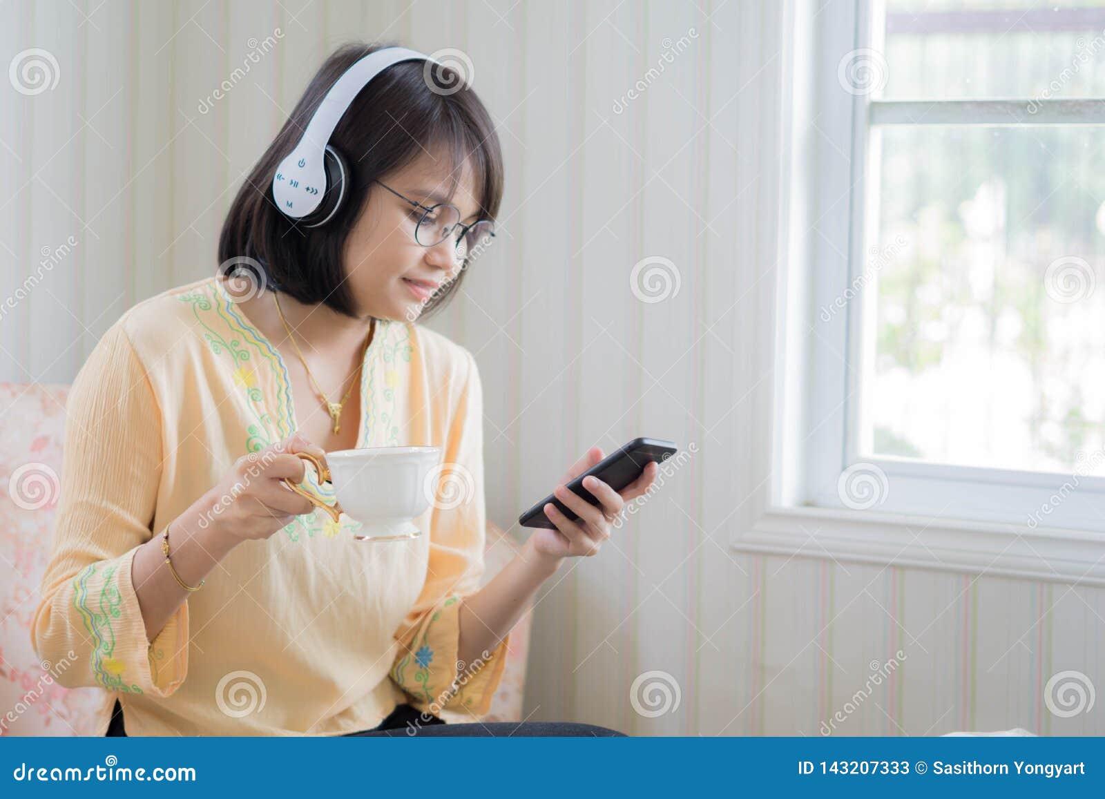 Härlig kvinna med hörlurar och smartphonen som kopplar av på