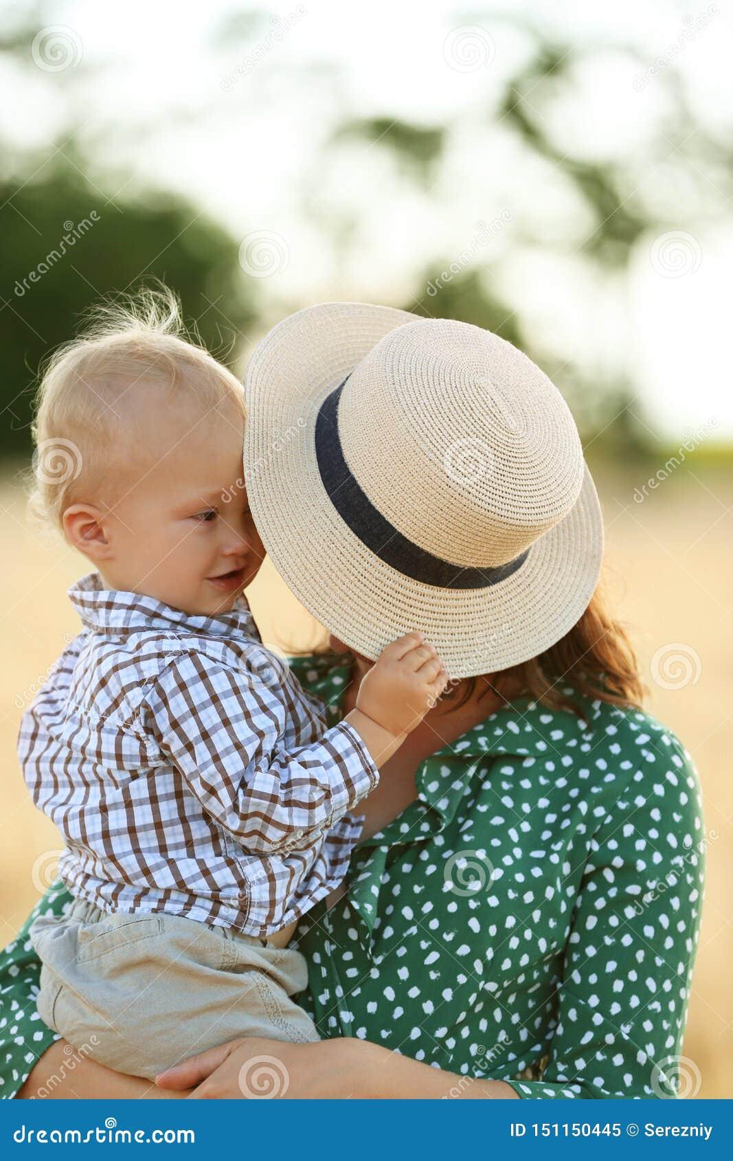 Härlig kvinna med hennes lilla son utomhus på sommardag
