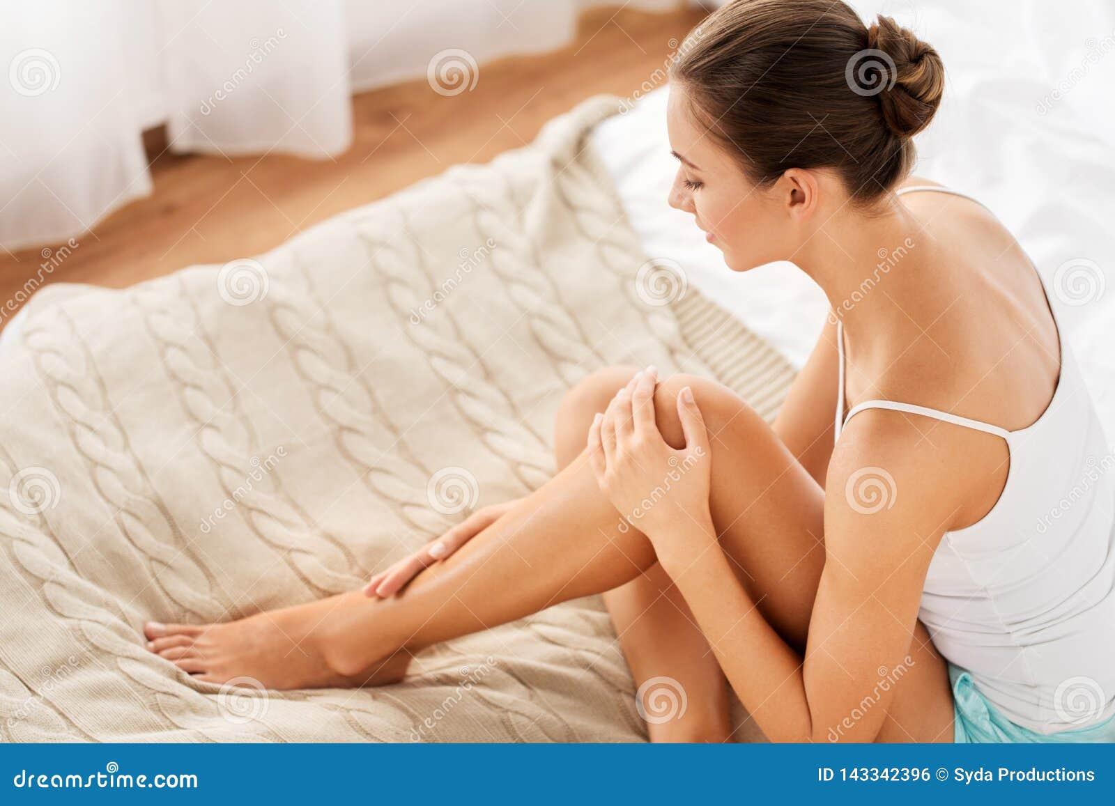 Härlig kvinna med kala ben på säng hemma