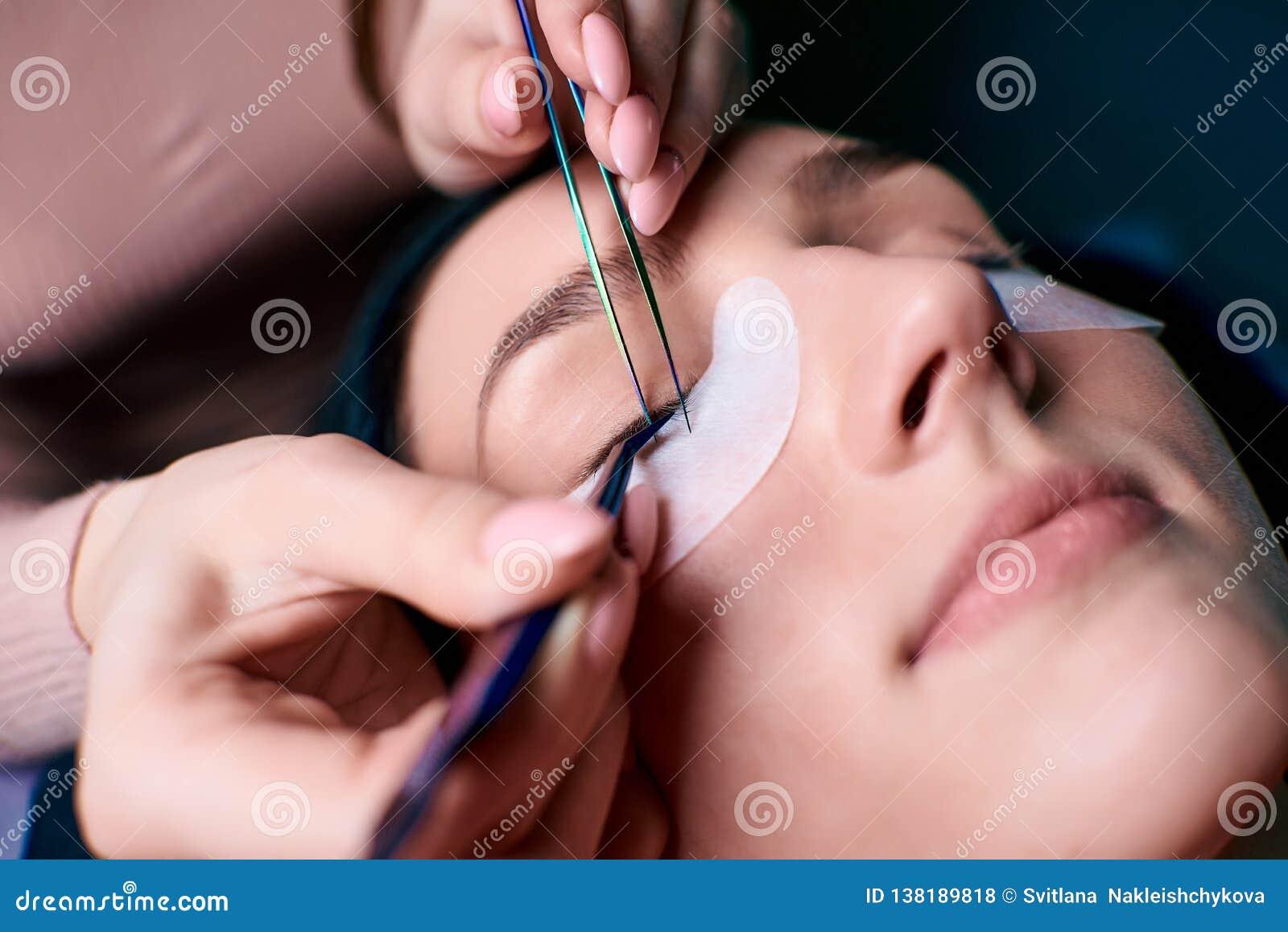 Härlig kvinna med långa ögonfrans i en skönhetsalong Ögonfransförlängningstillvägagångssätt Snärtar stänger sig upp