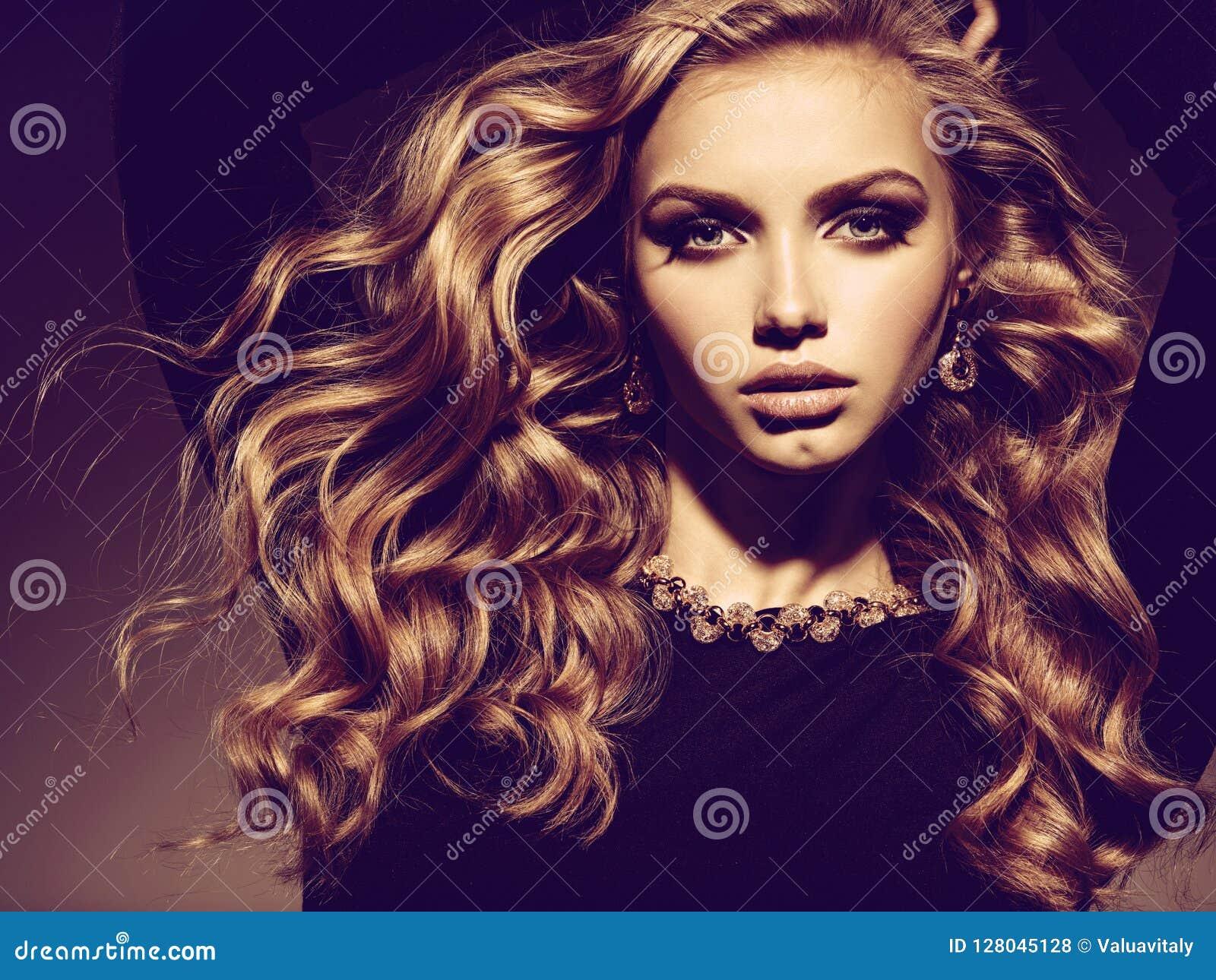 Härlig kvinna med långa lockigt hår- och guldsmycken
